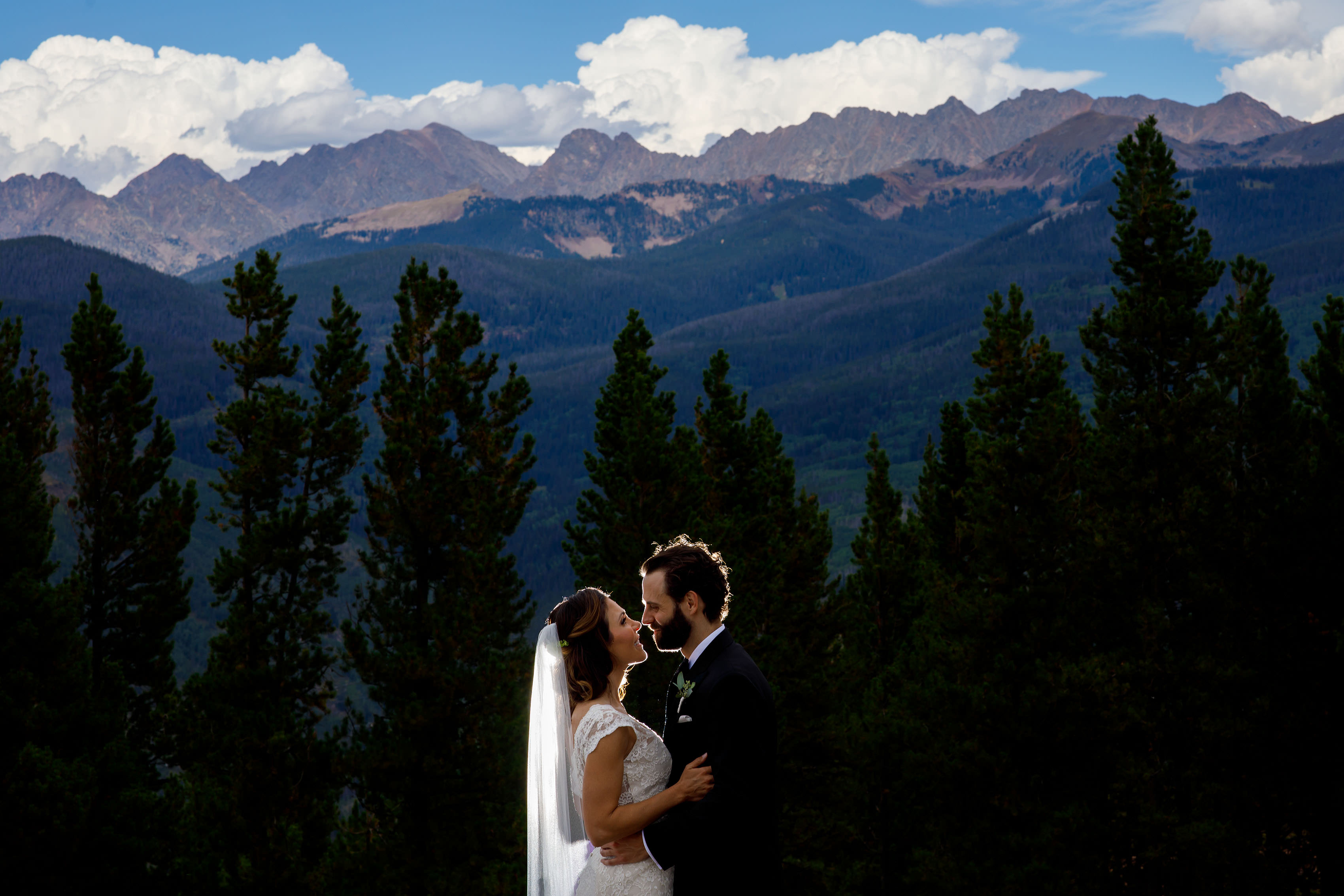A couple poses on front of the Gore range atop Vail before their Vail Golf Club Wedding