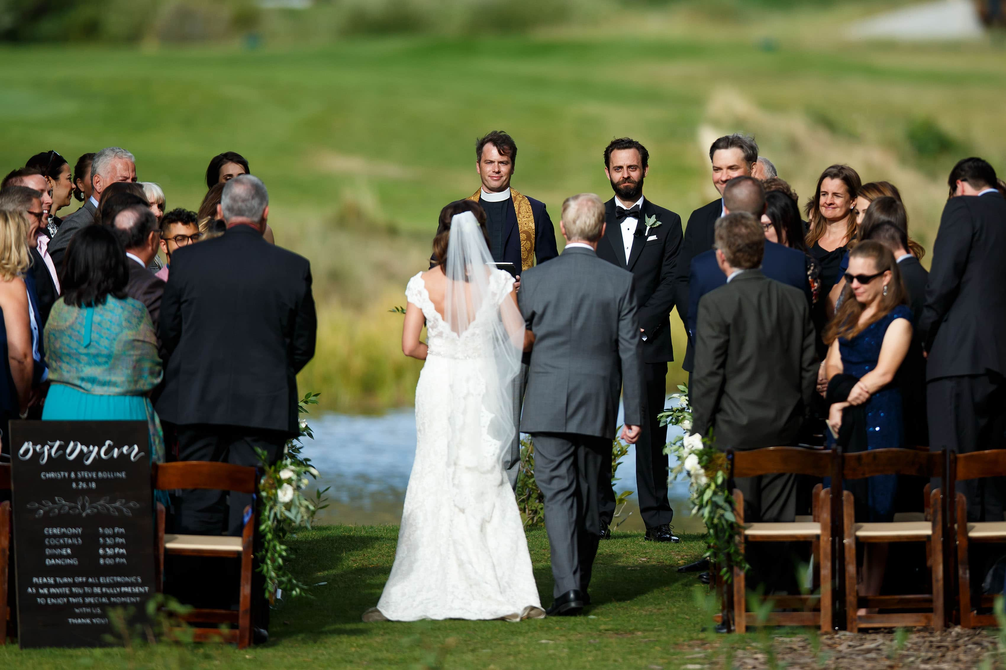 The groom looks at his bride walking down the aisle during their Vail Golf Club wedding