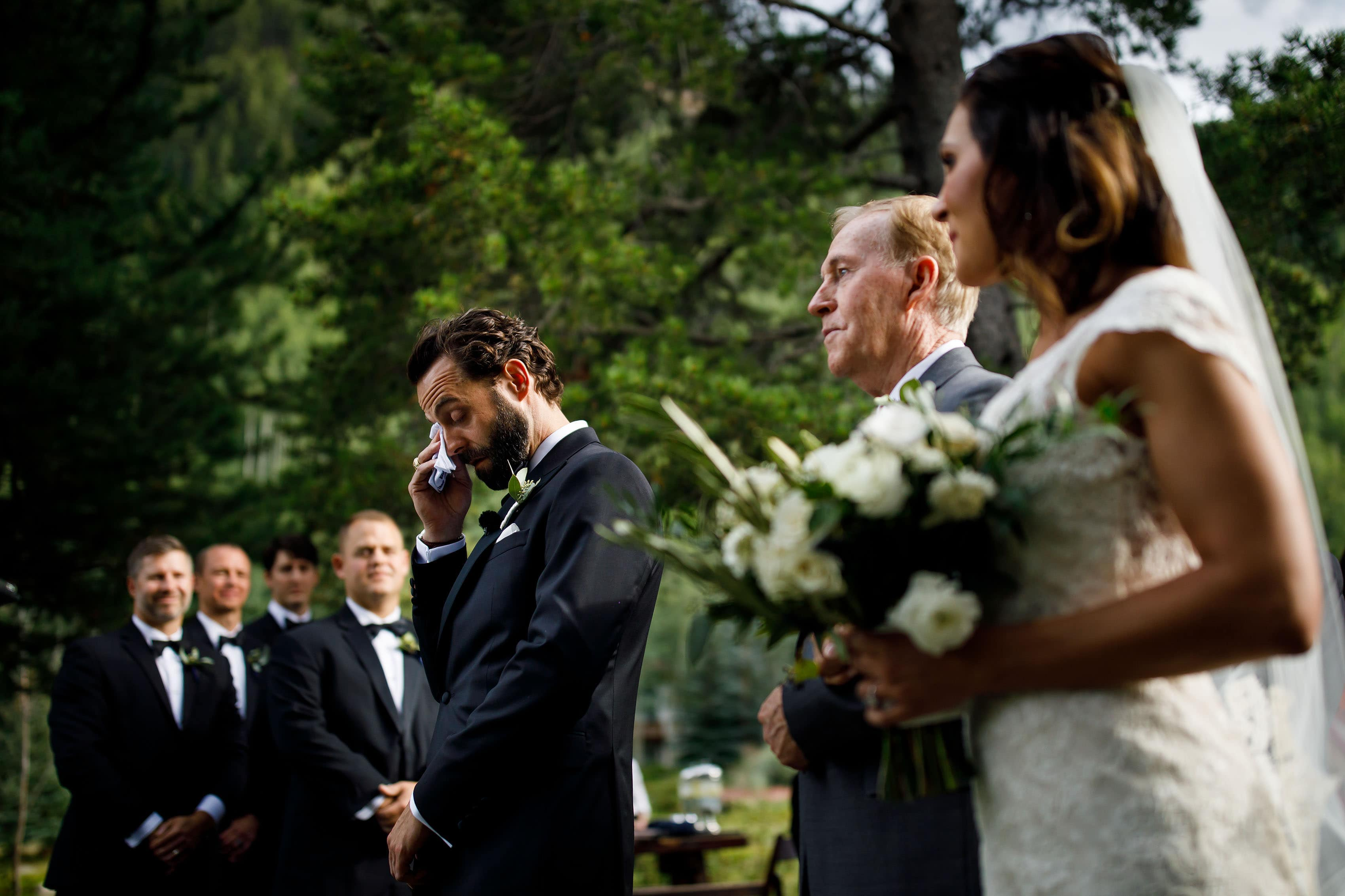 The groom wipes away a tear during the ceremony at Vail Golf Club