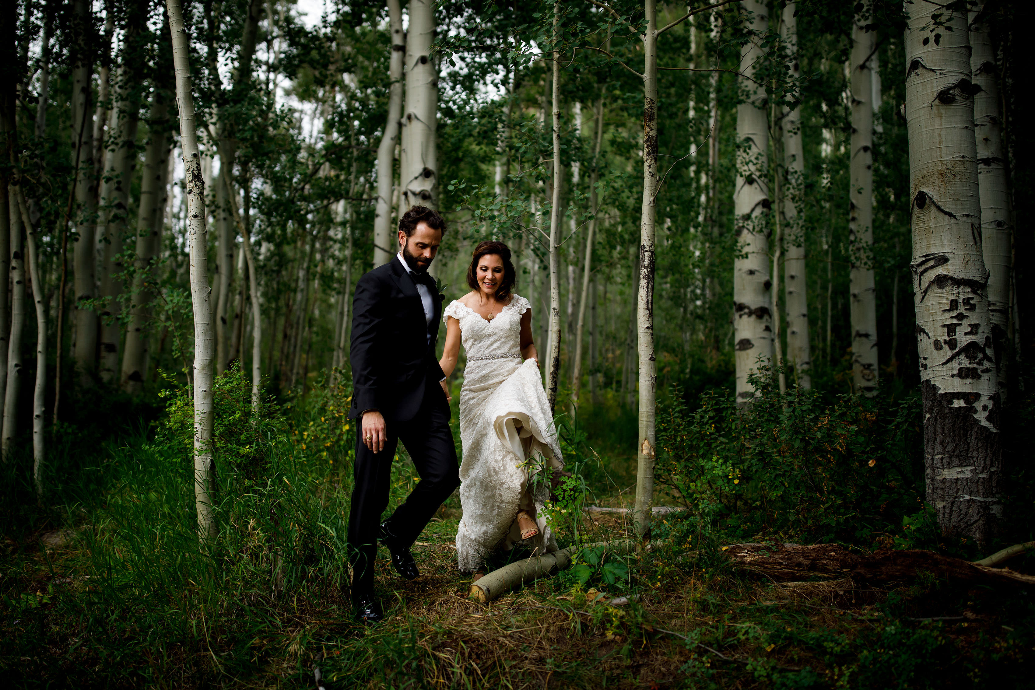The groom helps the bride out of a grove of aspen trees