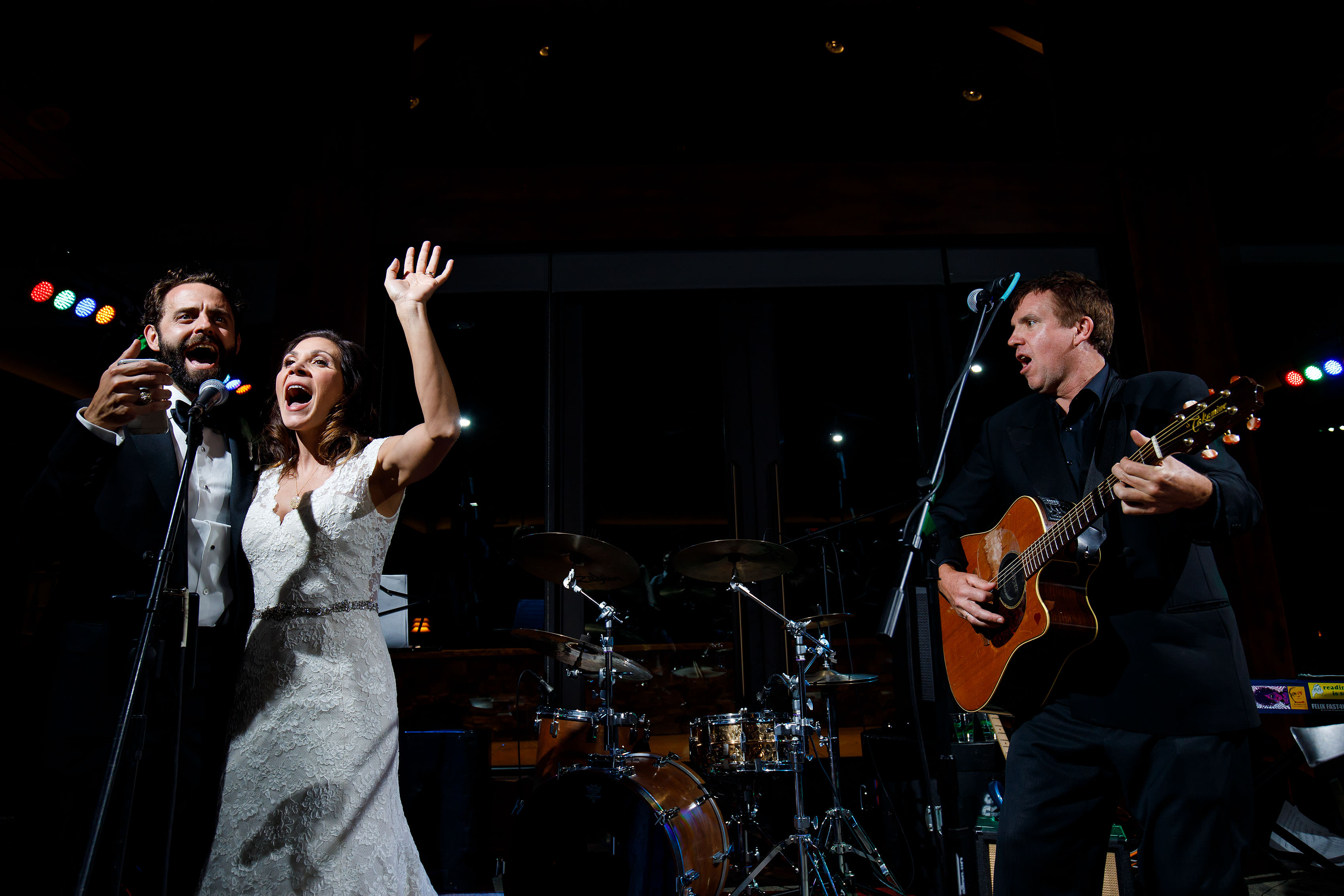 The bride and groom sing a song with the Jonny Mogambo Band during their Vail Golf Club Wedding
