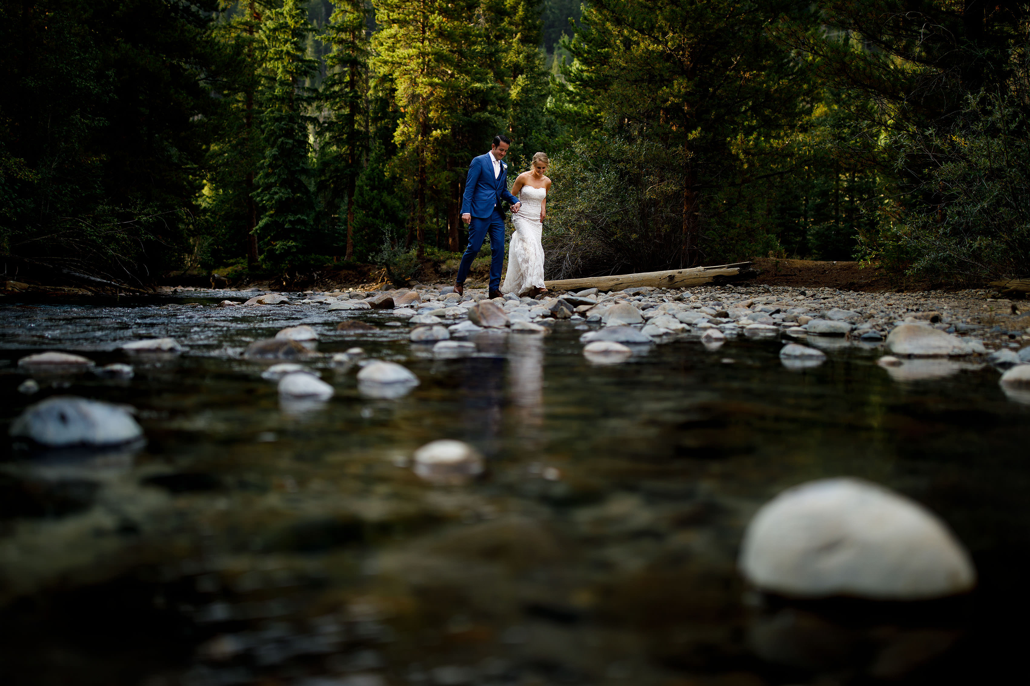 A couple walk together along the Snake River during their summer Keystone wedding