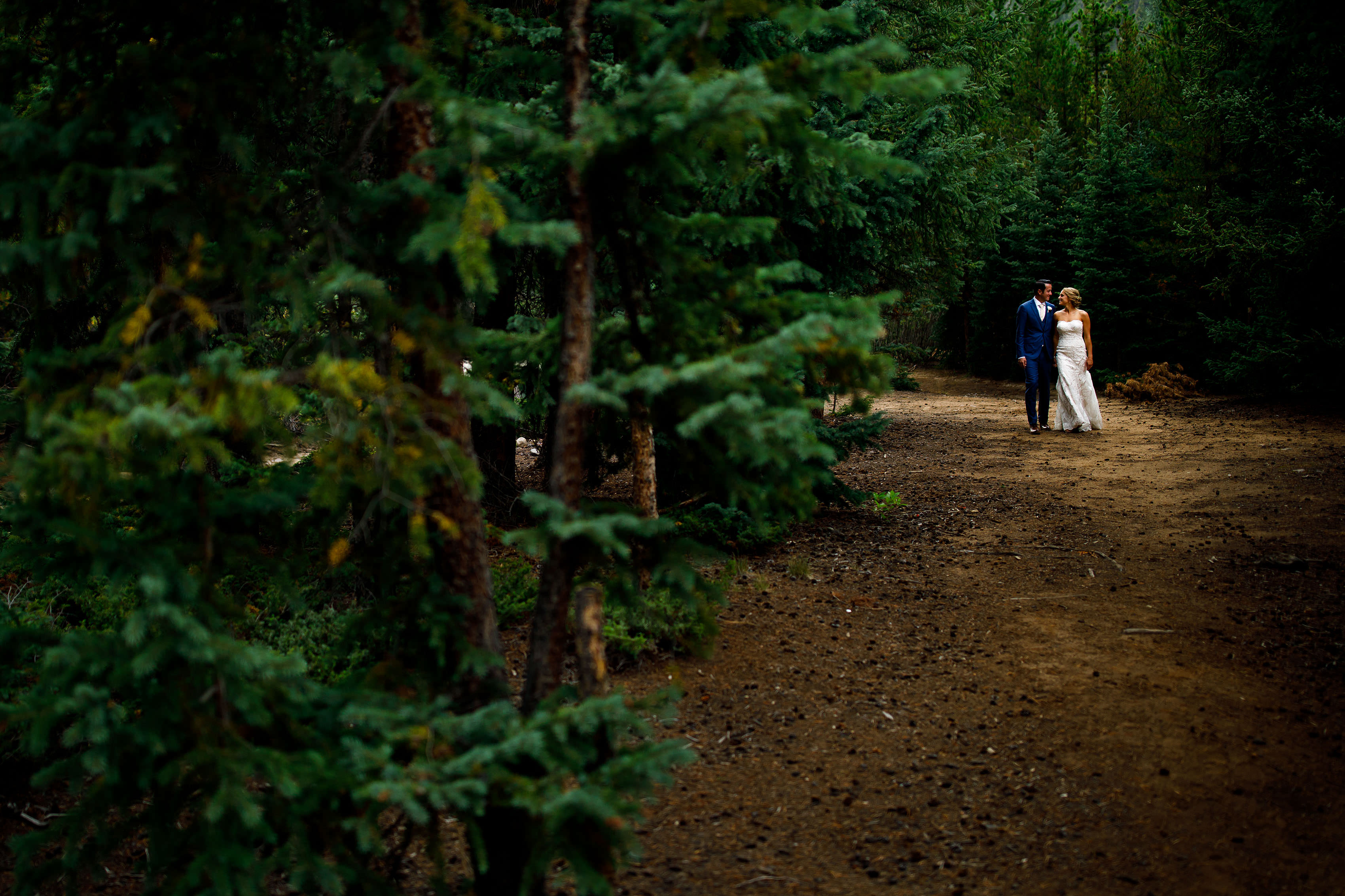 A couple walk together in the woods during their Keystone wedding