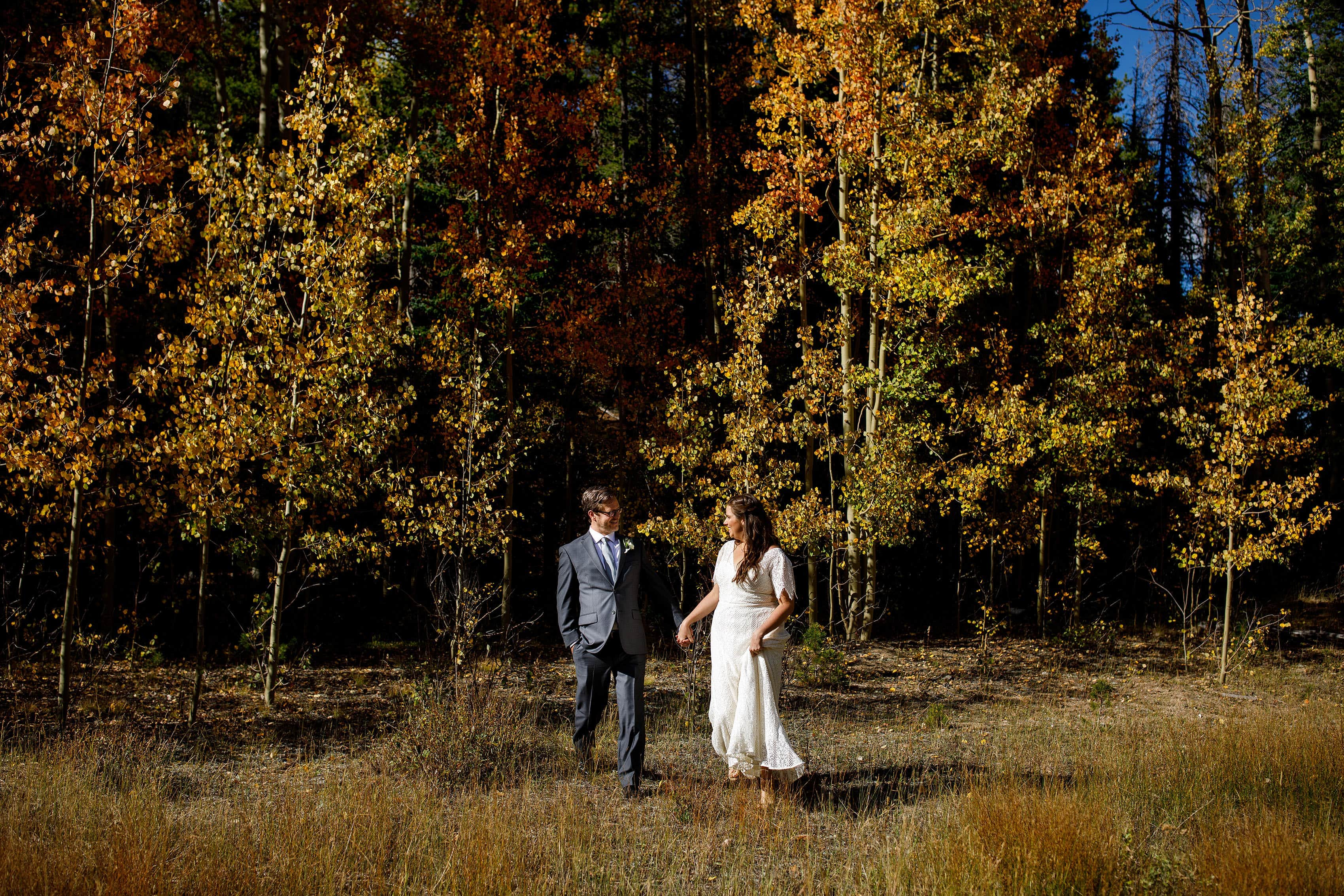 The newlyweds walk together near a grove of colorful aspen trees during their fall Blackstone Rivers Ranch wedding in Idaho Springs Colorado
