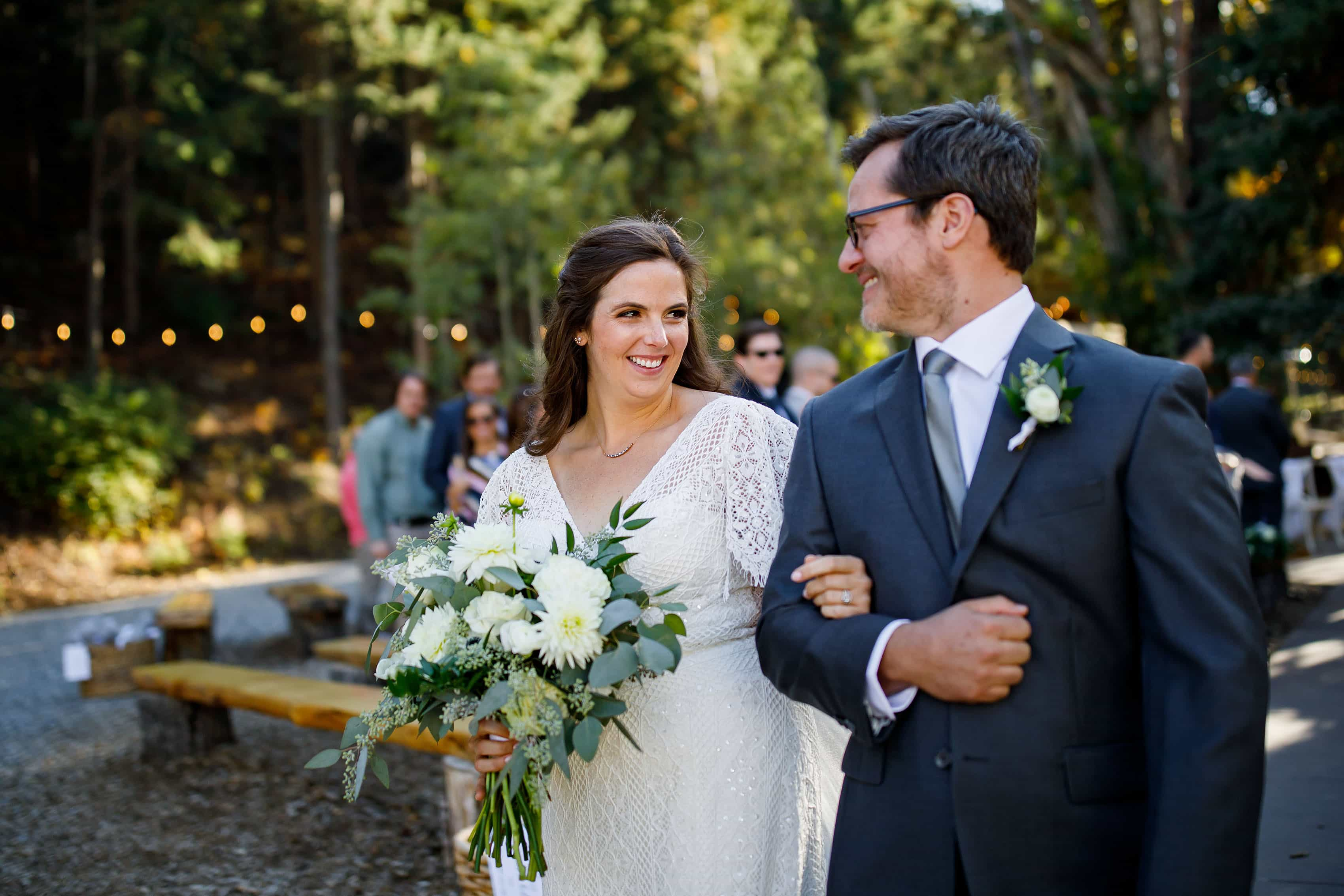 Kate smiles at Brian with her classic bouquet after their wedding ceremony at Blackstone Rivers Ranch