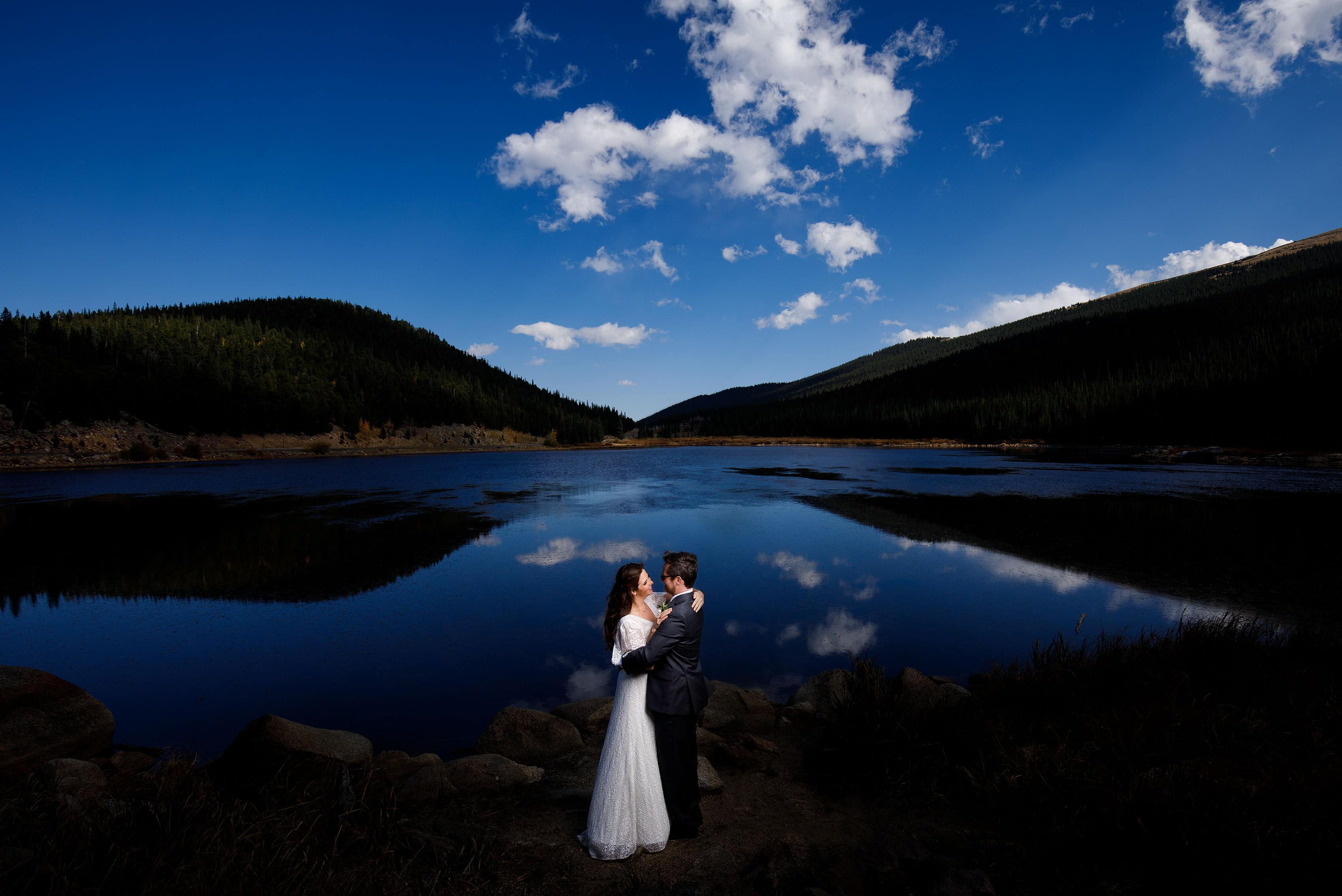 The couple poses at Echo Lake near Mount Evans after their fall Blackstone Rivers Ranch wedding in Idaho Springs Colorado
