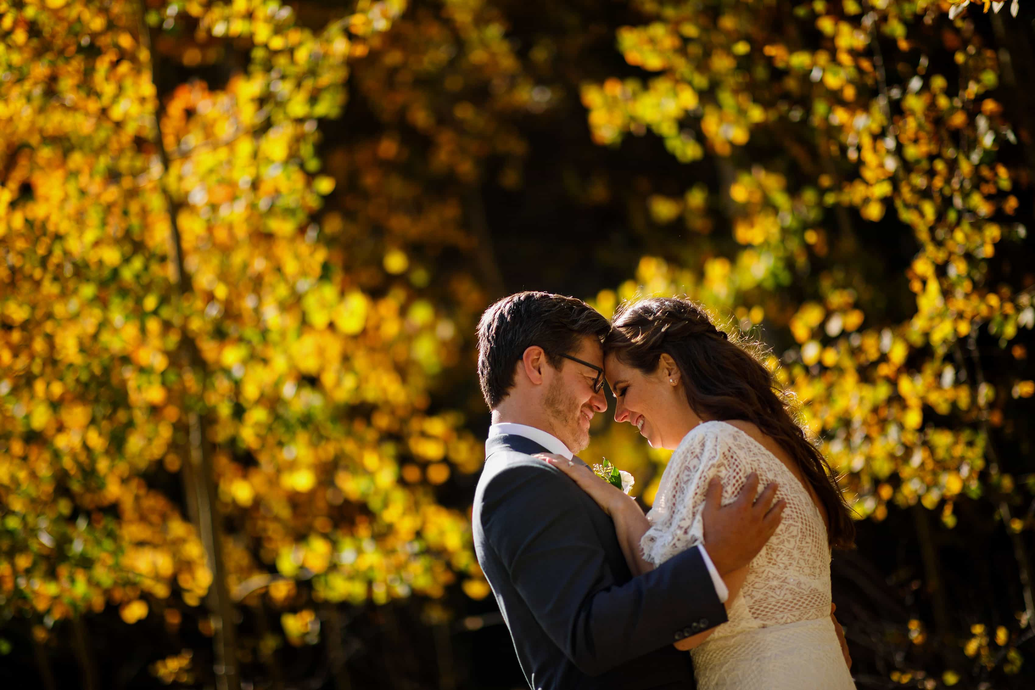 Kate and Brian embrace near a grove of yellow aspen trees after their fall wedding in Idaho Springs at Blackstone Rivers Ranch