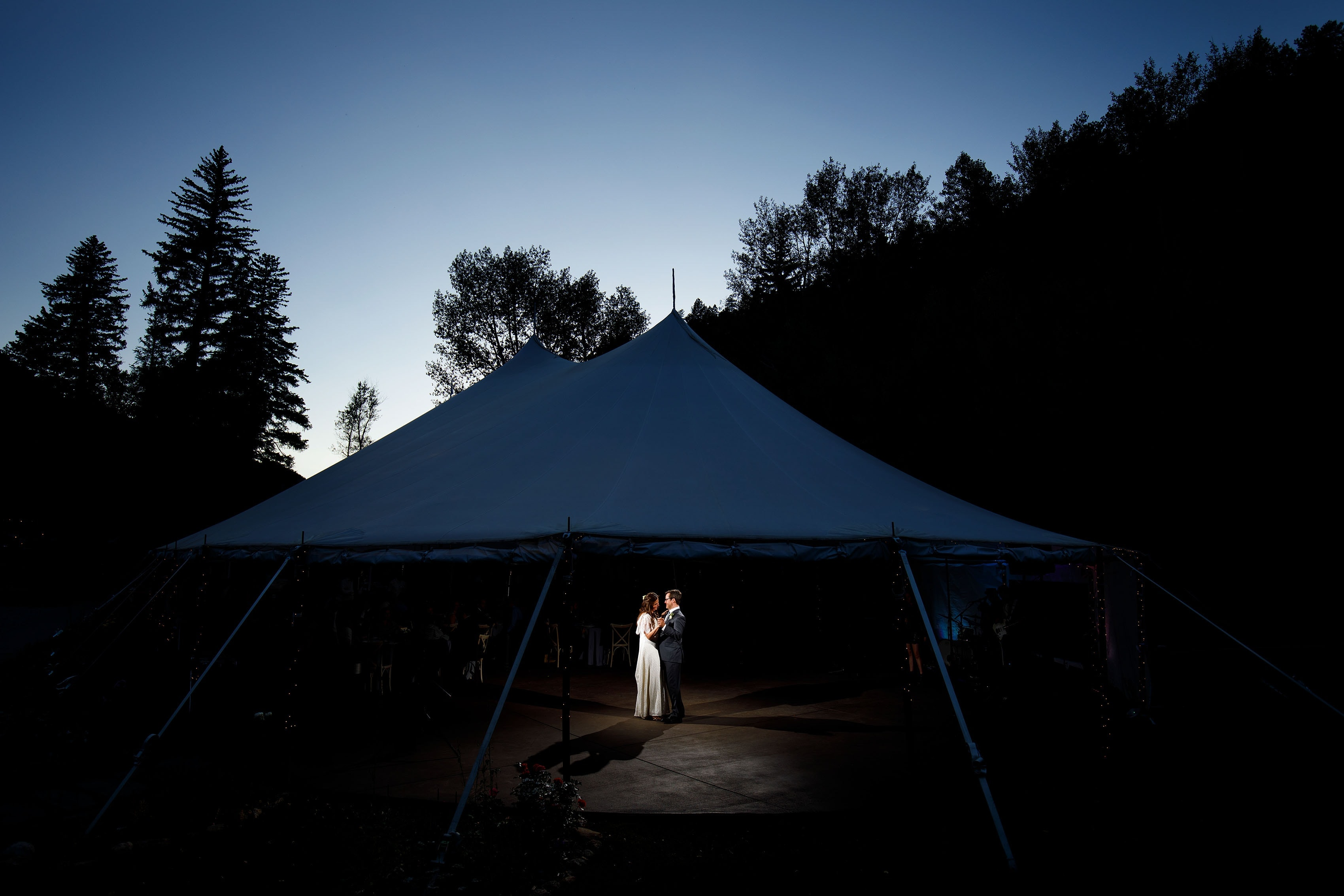 Kate and Brian share a first dance under the tent during twilight at Blackstone Rivers Ranch