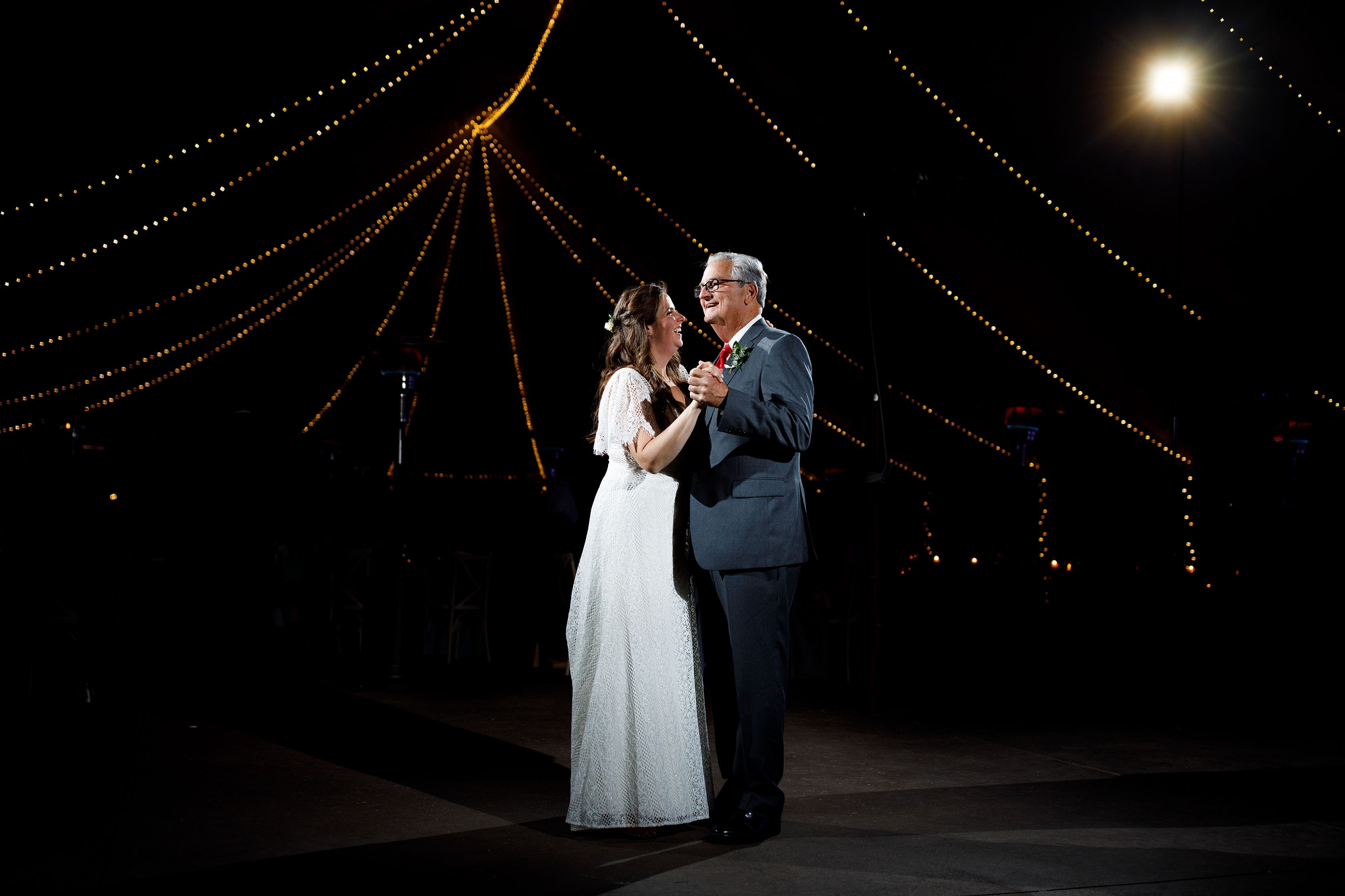 The bride dances with her father under the tent at Blackstone Rivers Ranch during her fall wedding