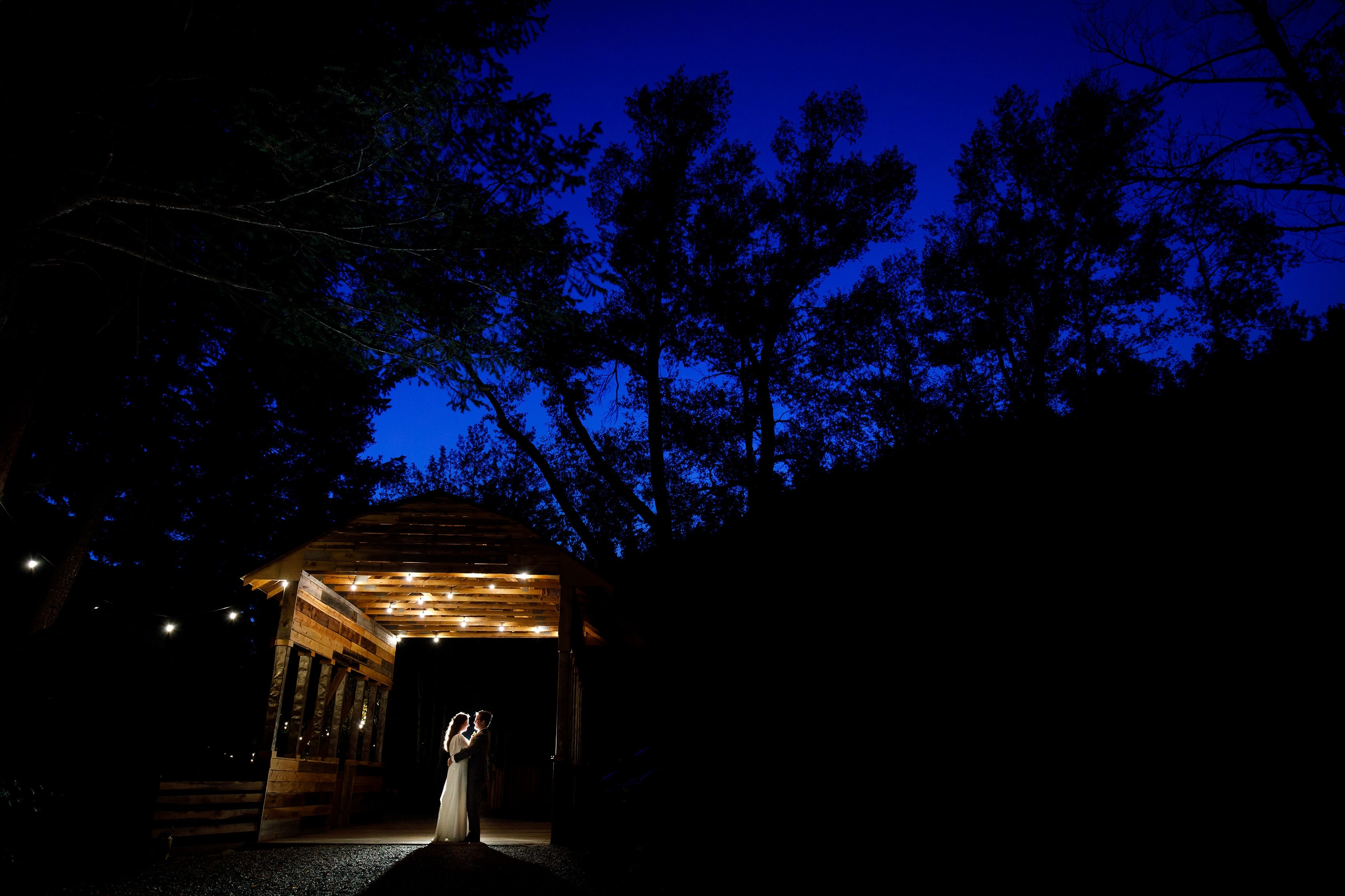 The bride and groom post under the covered bridge at twilight during their fall Blackstone Rivers Ranch wedding