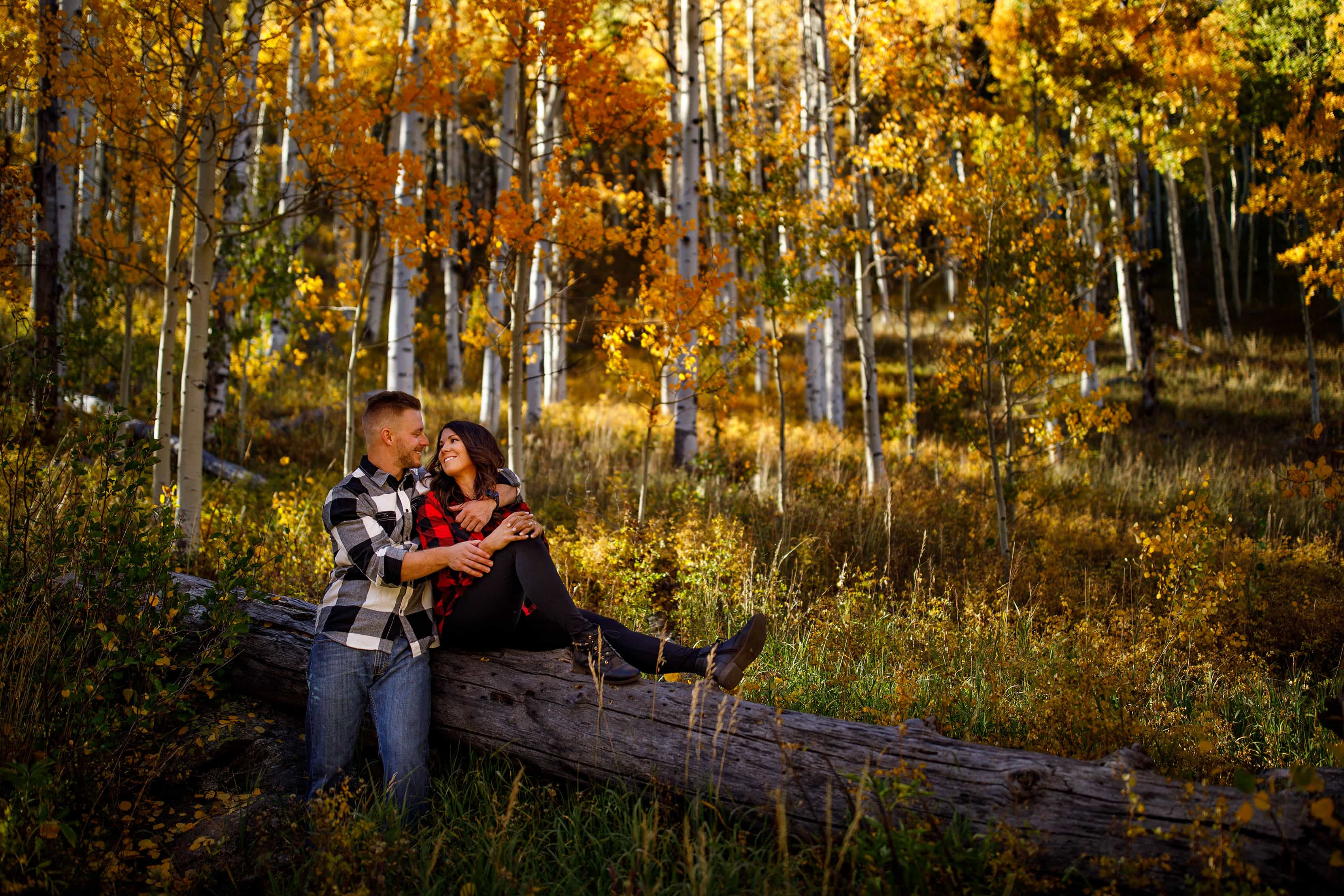 Caroline and Brendan pose near yellow aspen trees at Piney River Ranch