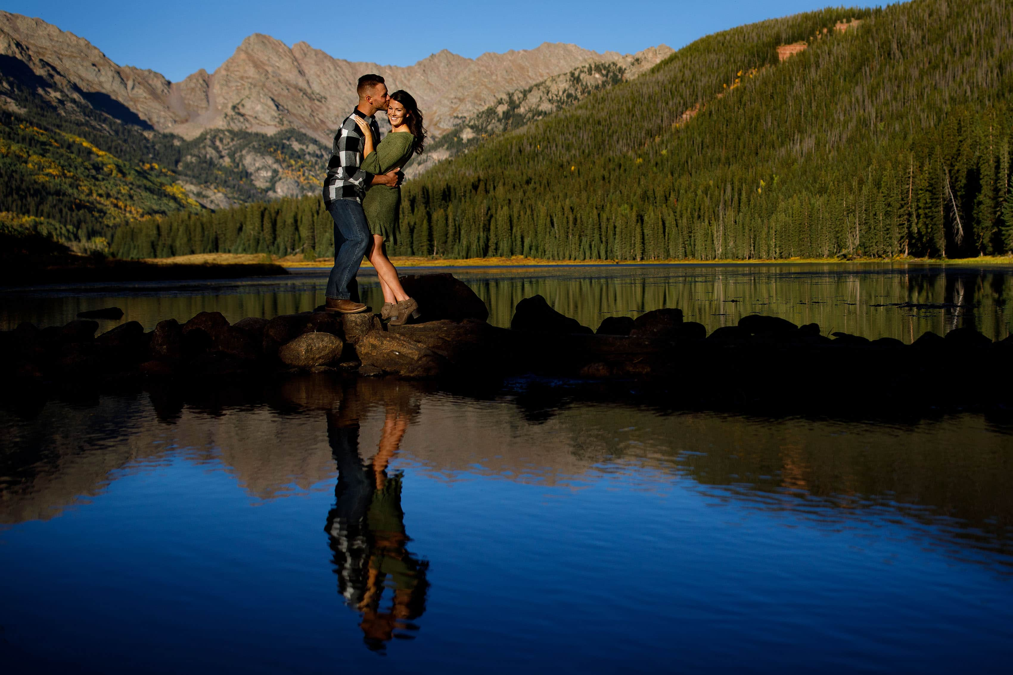 Brendan kisses Caroline near the water edge at Piney River Ranch during their engagement session in Vail