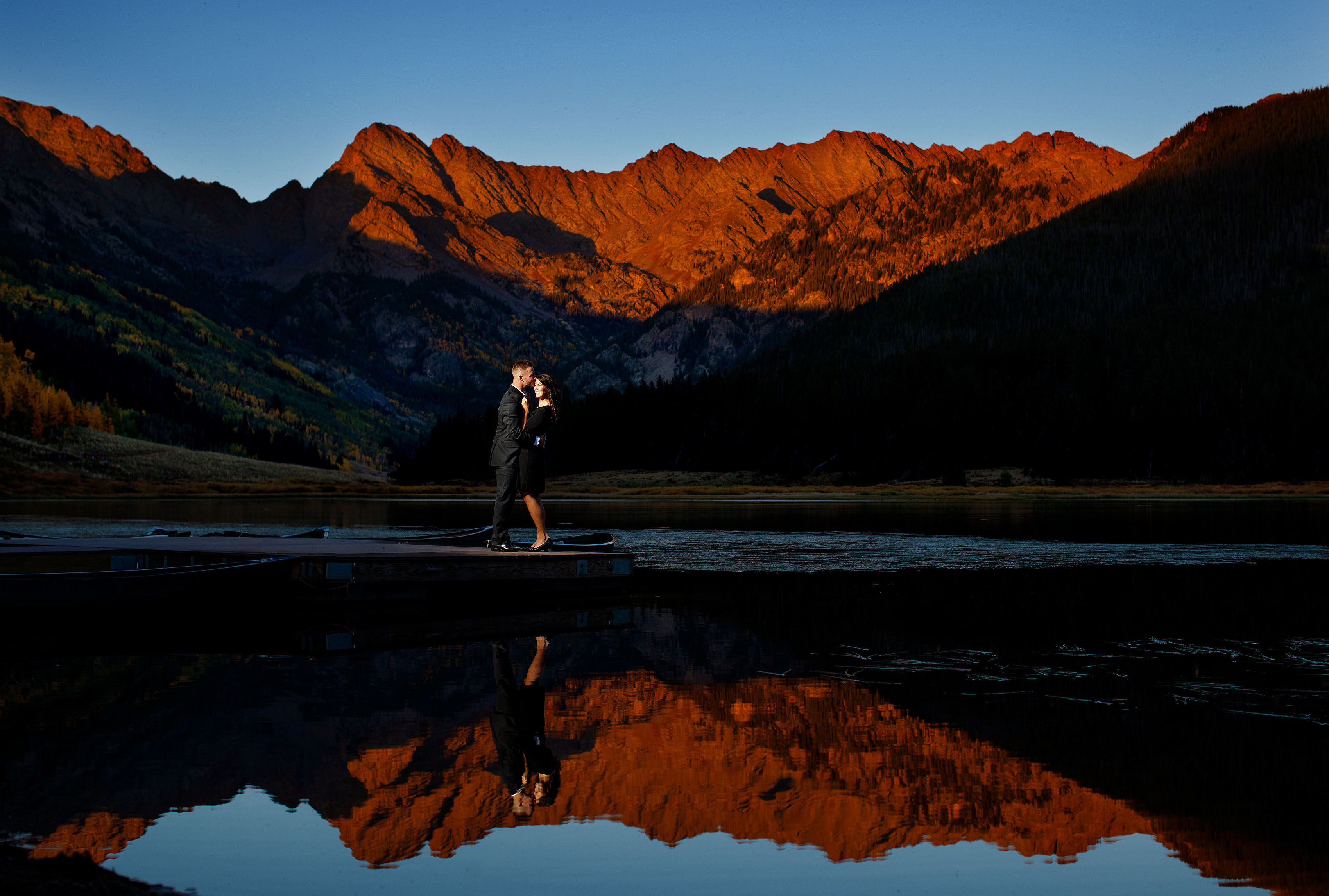 Brendan and Caroline pose on the dock as the sun sets on the Gore mountain range during their fall Piney River Ranch engagement in Vail Colorado