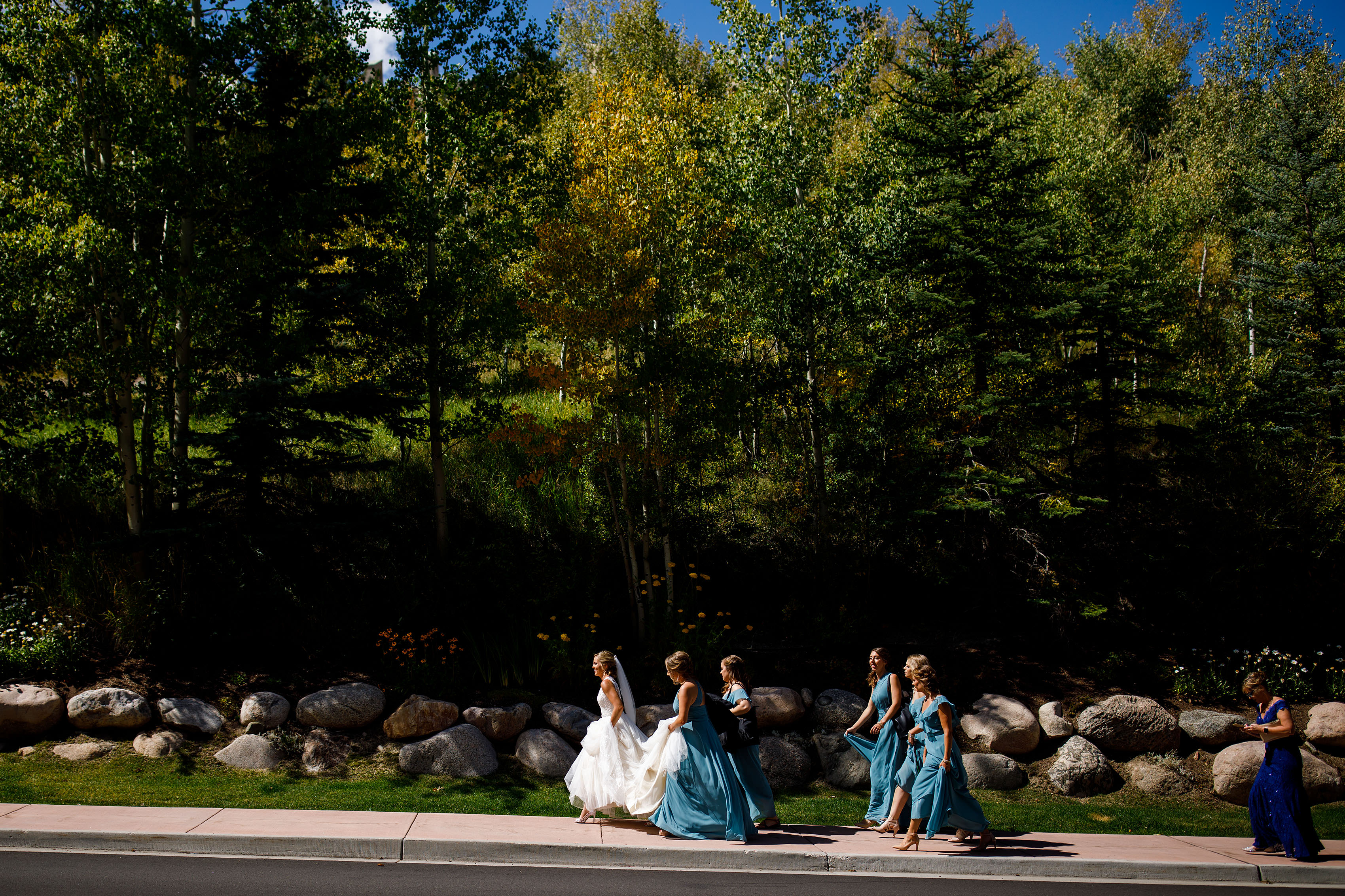 The bride walks with her bridesmaids to the Chapel at Beaver Creek before her fall wedding