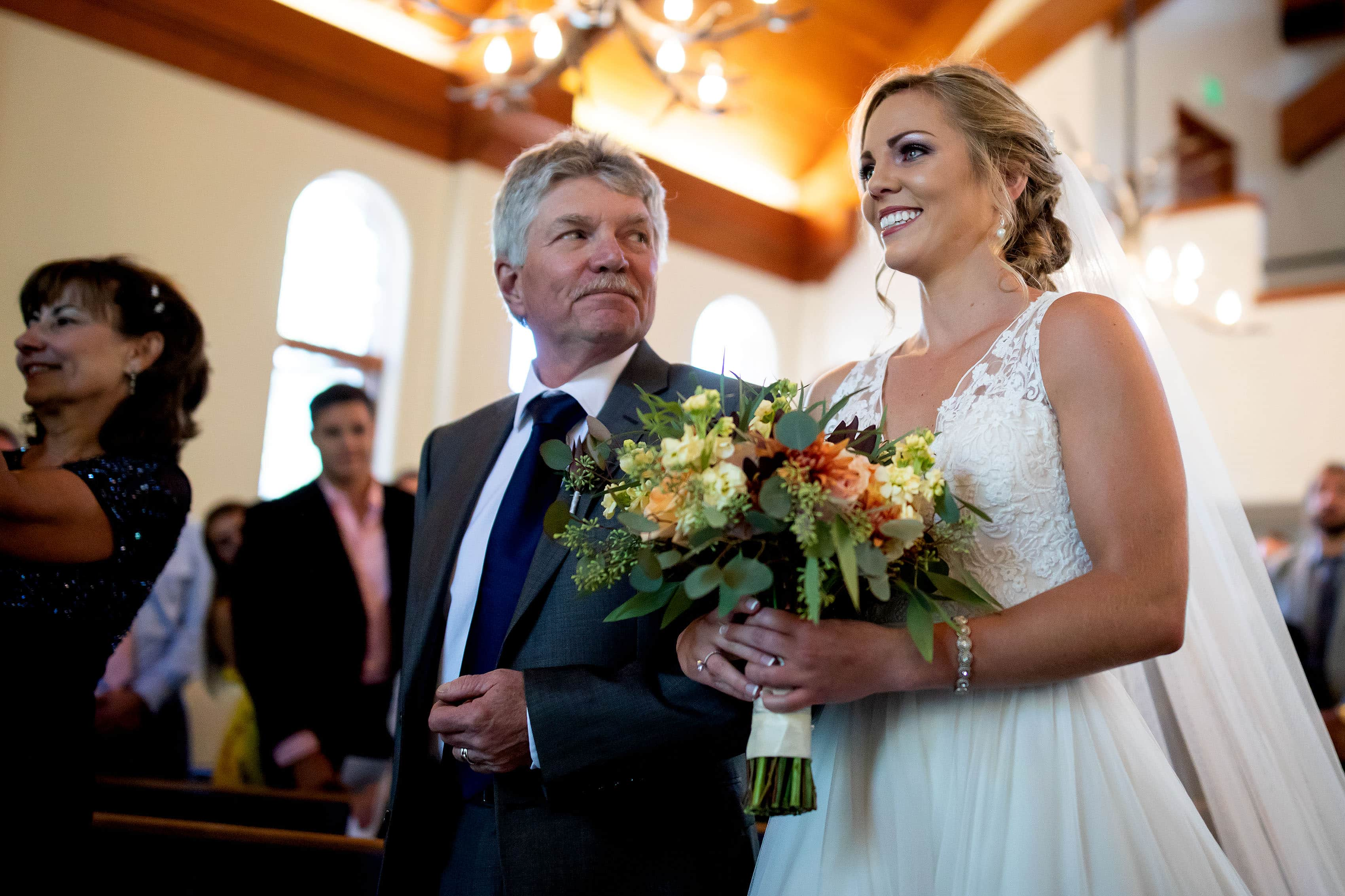 The bride becomes emotional while walking down the aisle with her father during a wedding at the Capel at Beaver Creek