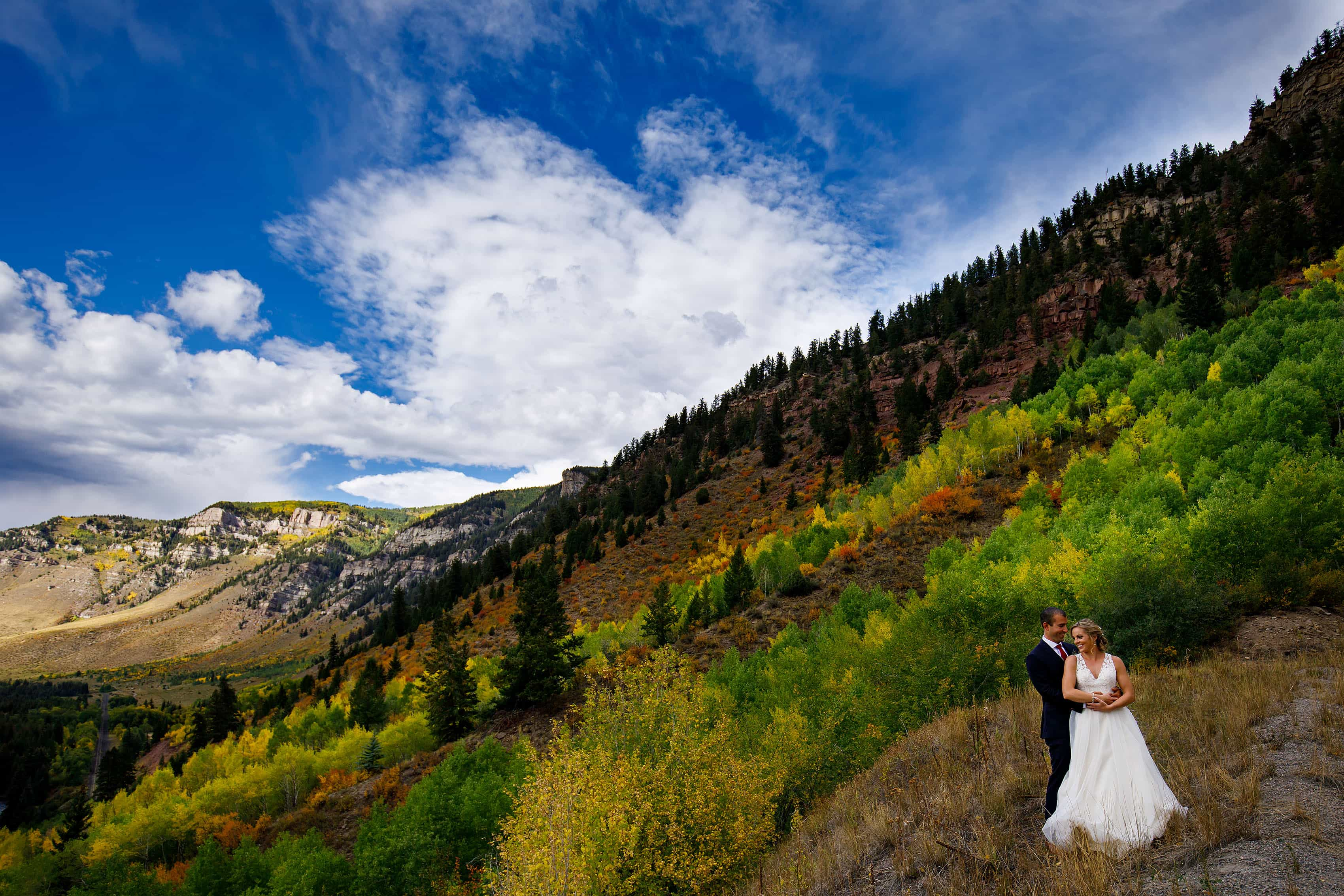 A couple embrace along the 10th mountain division memorial highway near a grove of colorful aspen trees in the fall during their Camp Hale wedding