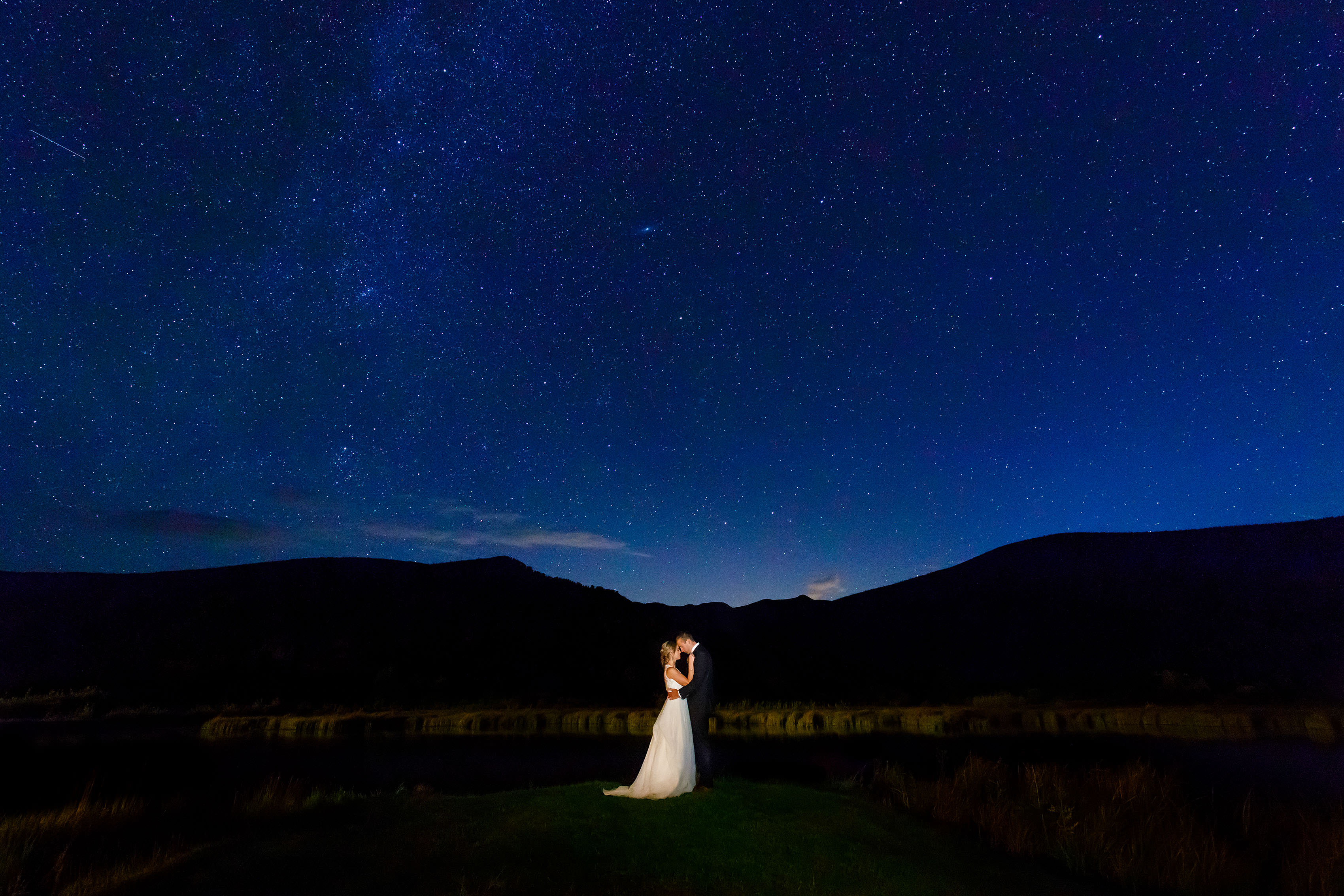 Meghan and Kevin embrace under the stars during their fall wedding at Camp Hale in Colorado