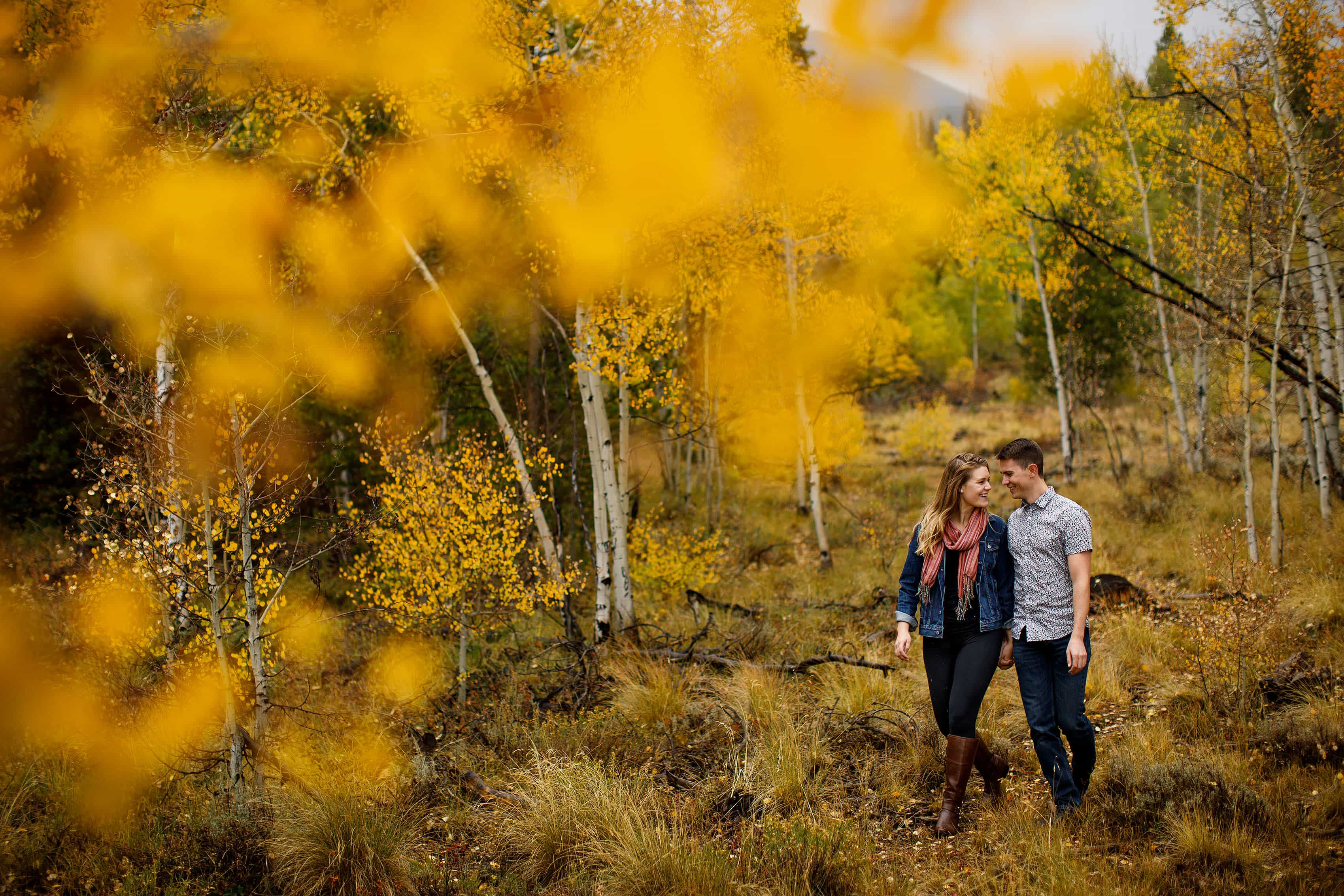 Holly and Hayden walk in a grove of aspen trees near Meadow Creek Trailhead in Frisco during their engagement photos