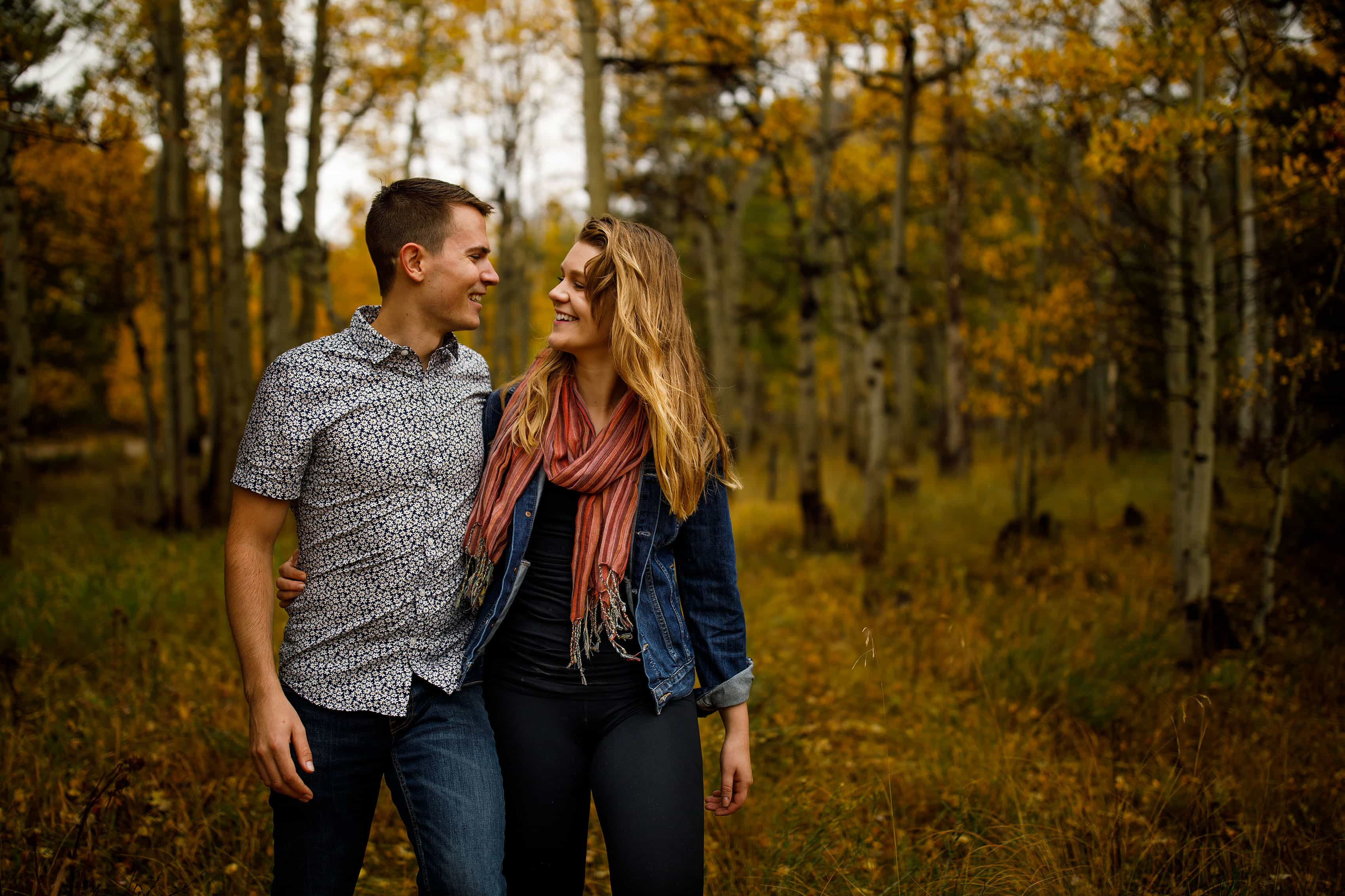 A couple walk together near Frisco Colorado in the fall to celebrate their engagement