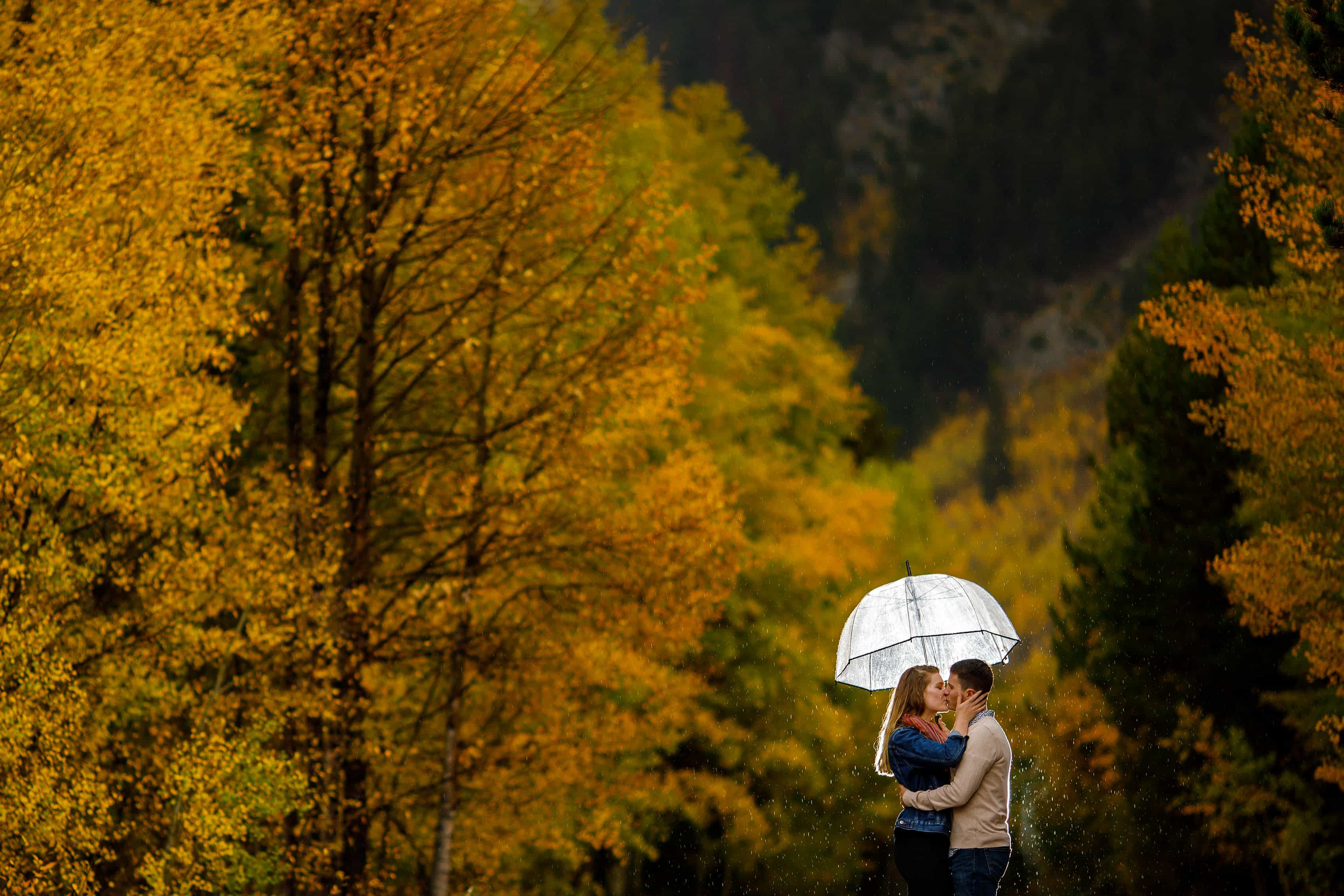 Holly and Hayden kiss under an umbrella during a fall rain shower in Frisco Colorado during their engagement session