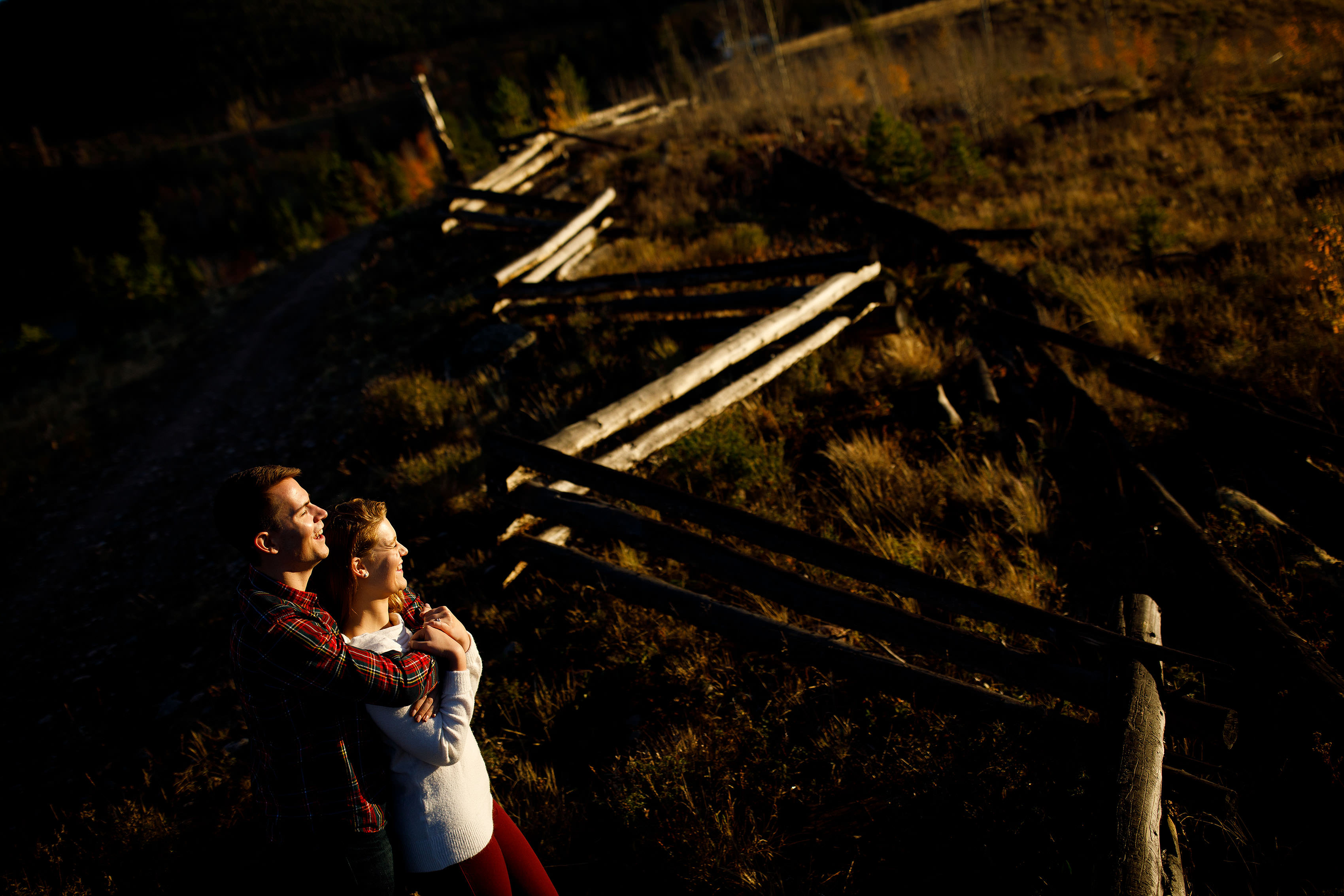 A couple pose near a wooden fence near Frisco