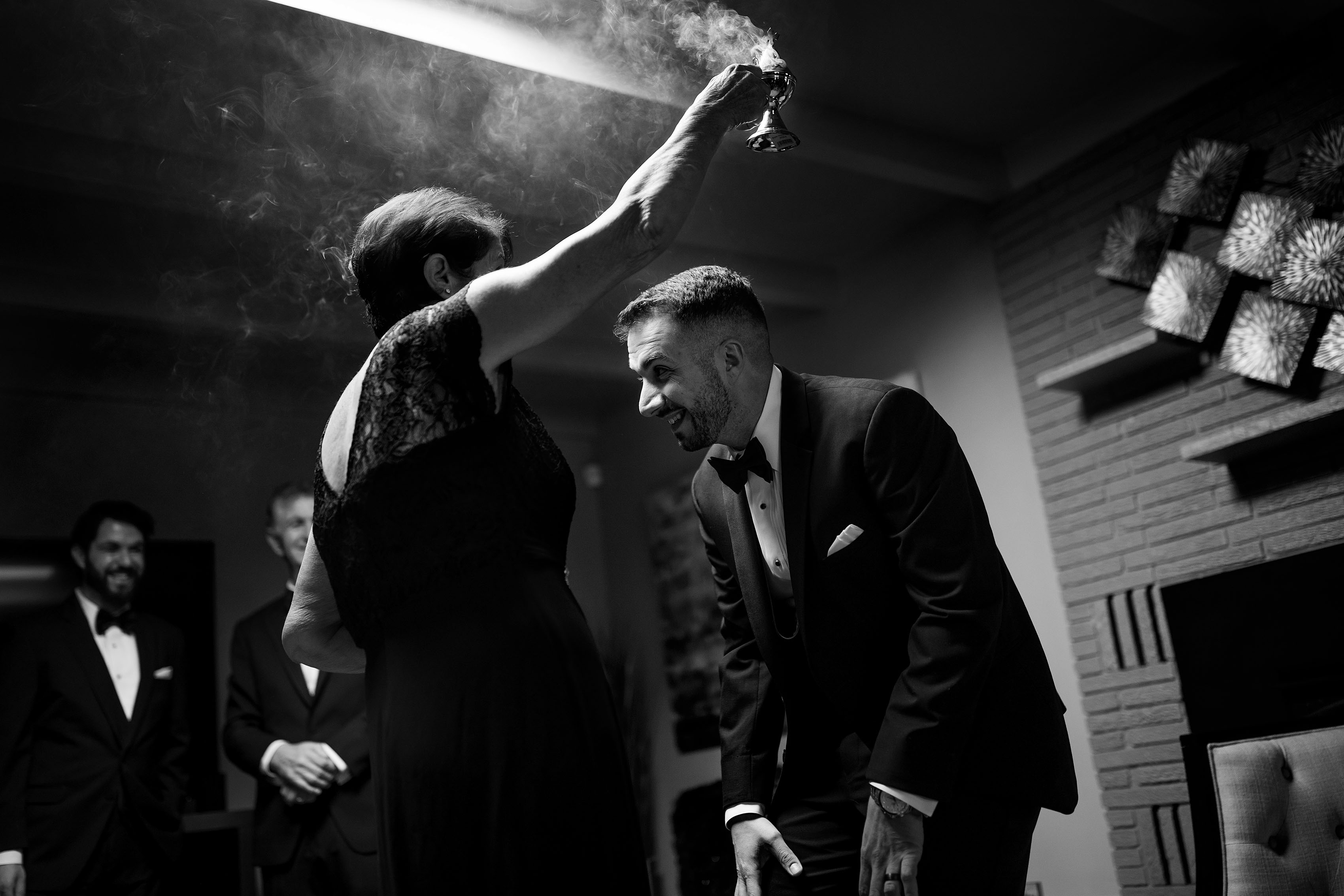 The groom's mother waves smoke during cypriot wedding traditions as the groom gets ready for the wedding