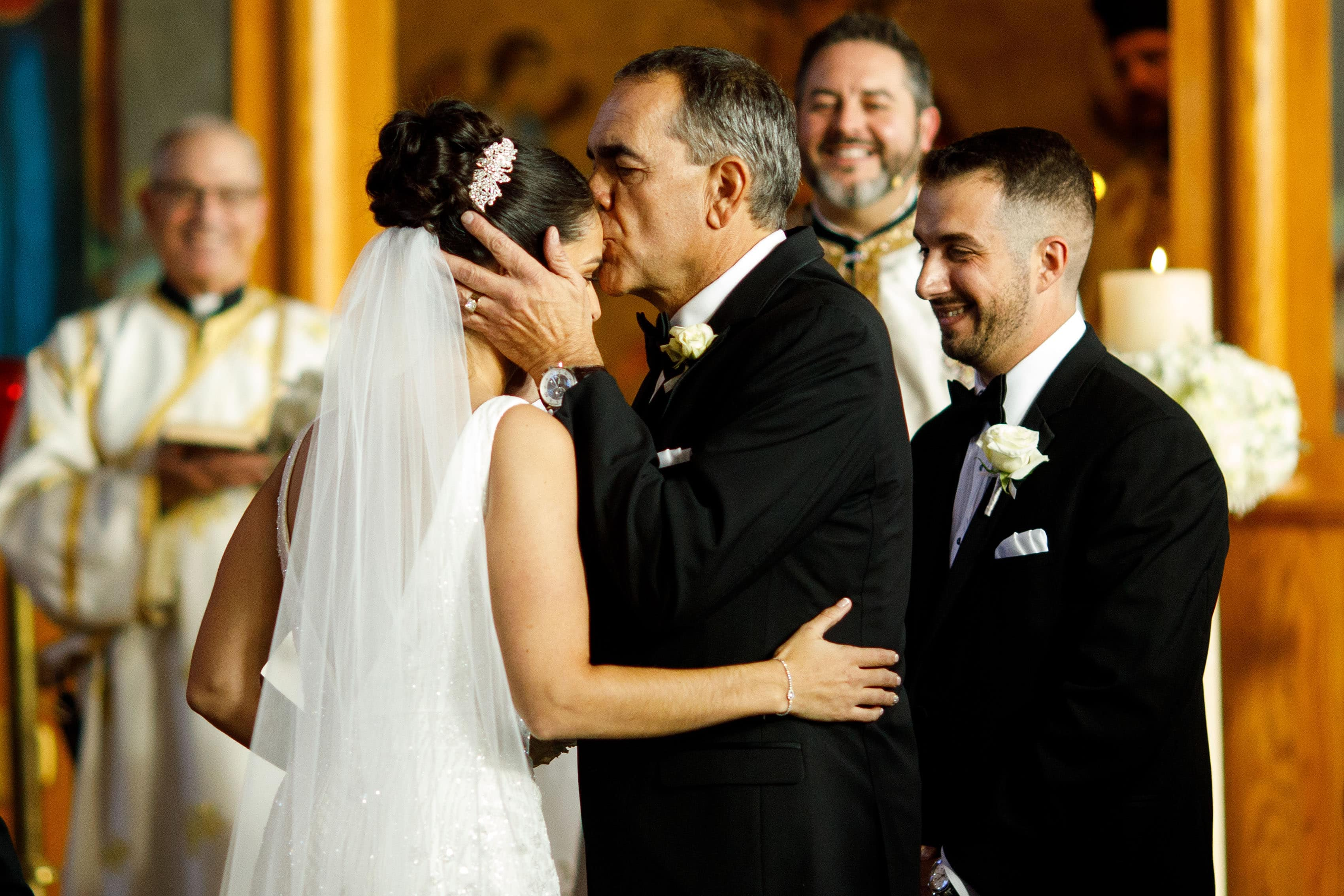 The father of the bride kisses his daughter