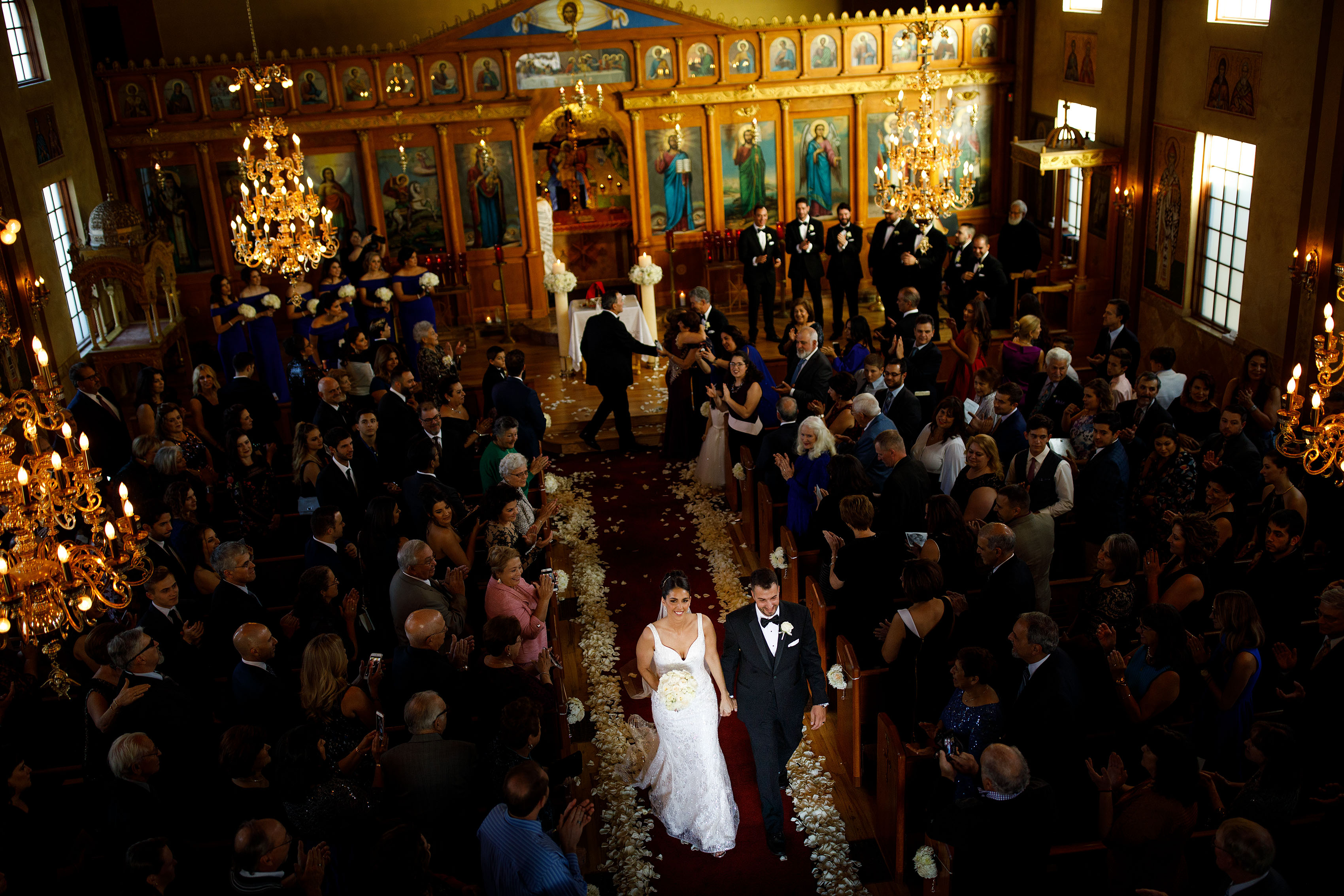 The bride and groom walk down the aisle during their Albuquerque Greek Orthodox wedding at Saint George
