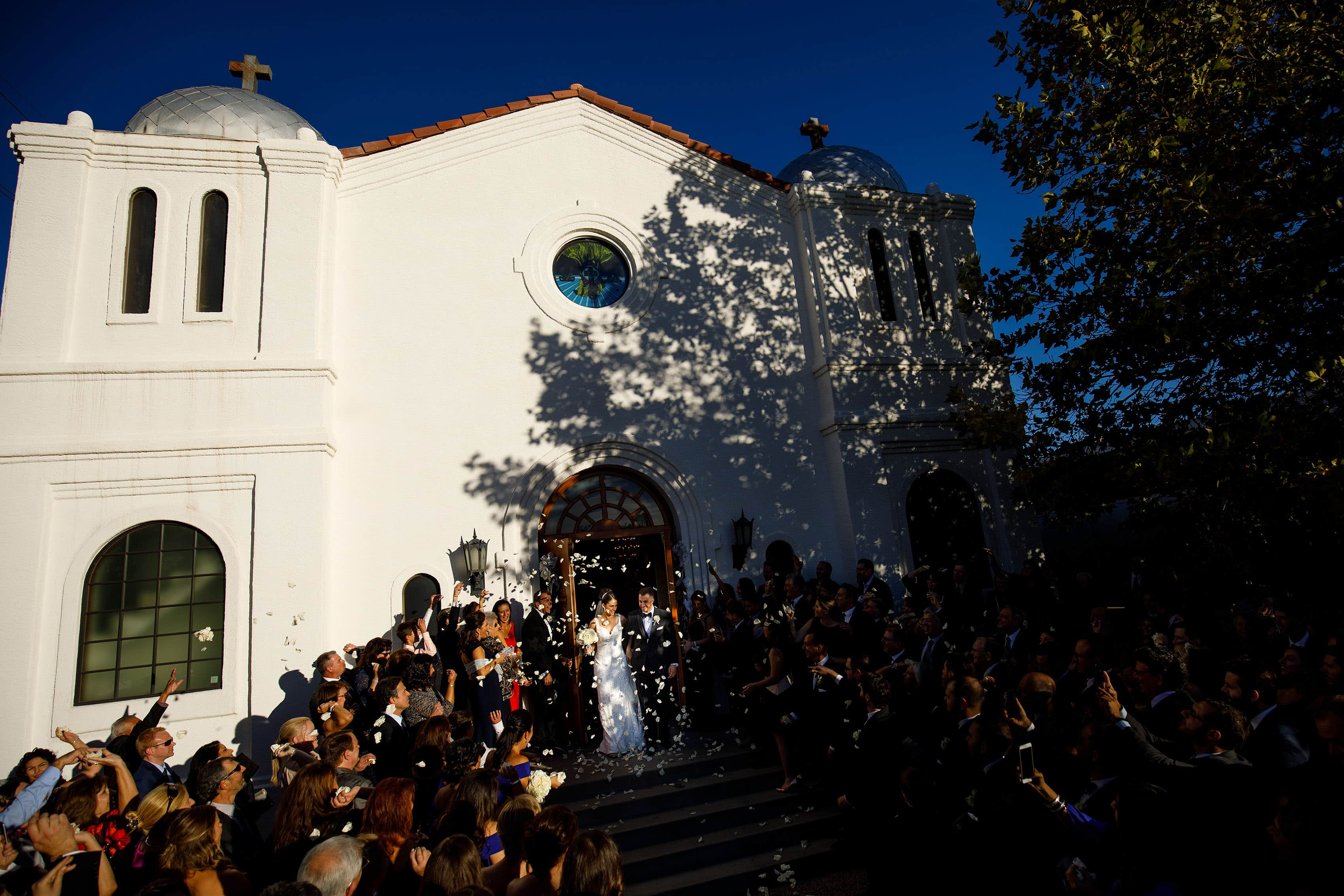 The bride and groom are showered with rose pedals as they exit Saint George Greek Orthodox Church during their Albuquerque wedding