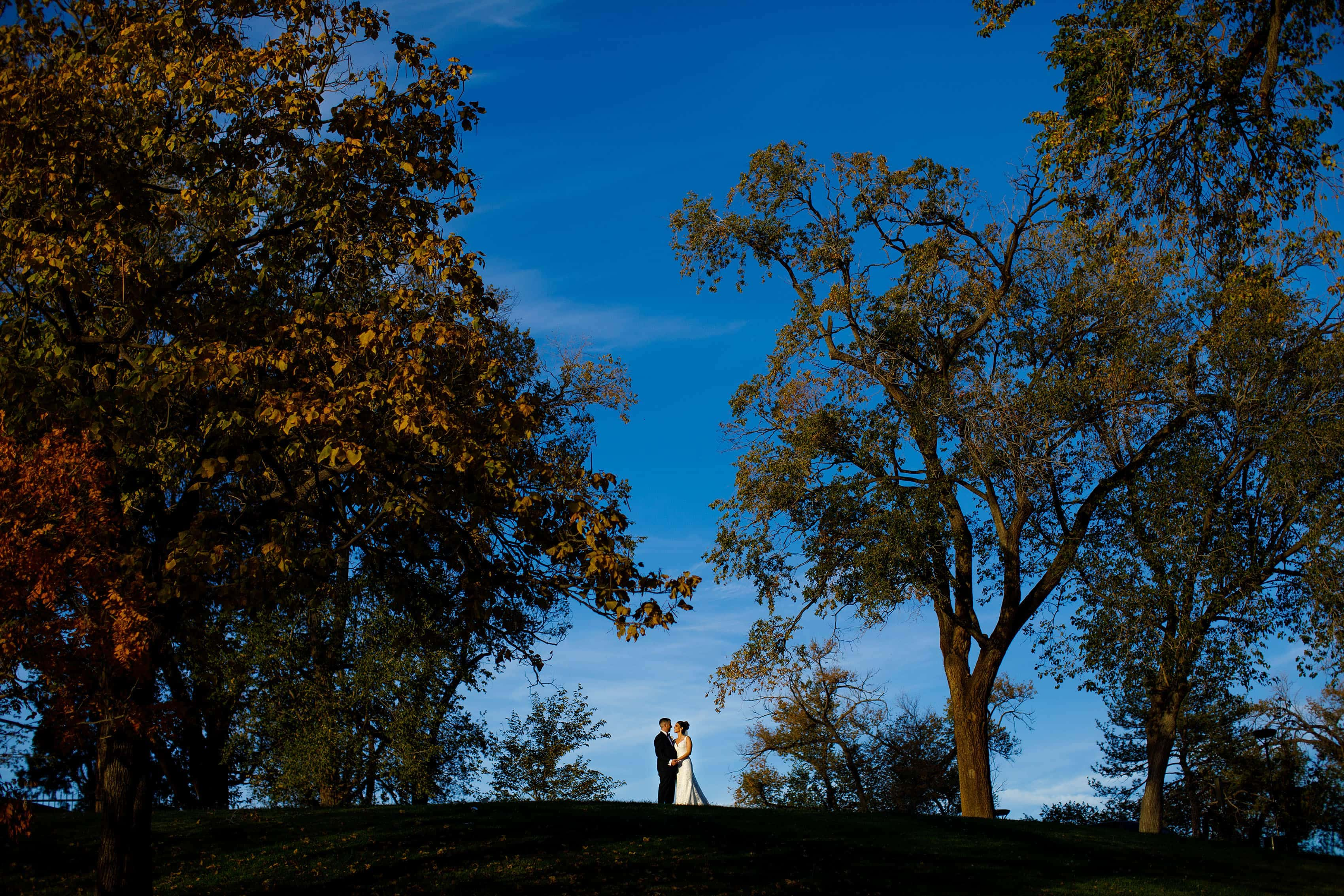 The bride and groom embrace on a fall day in Highland Park during their Albuquerque Greek Orthodox wedding