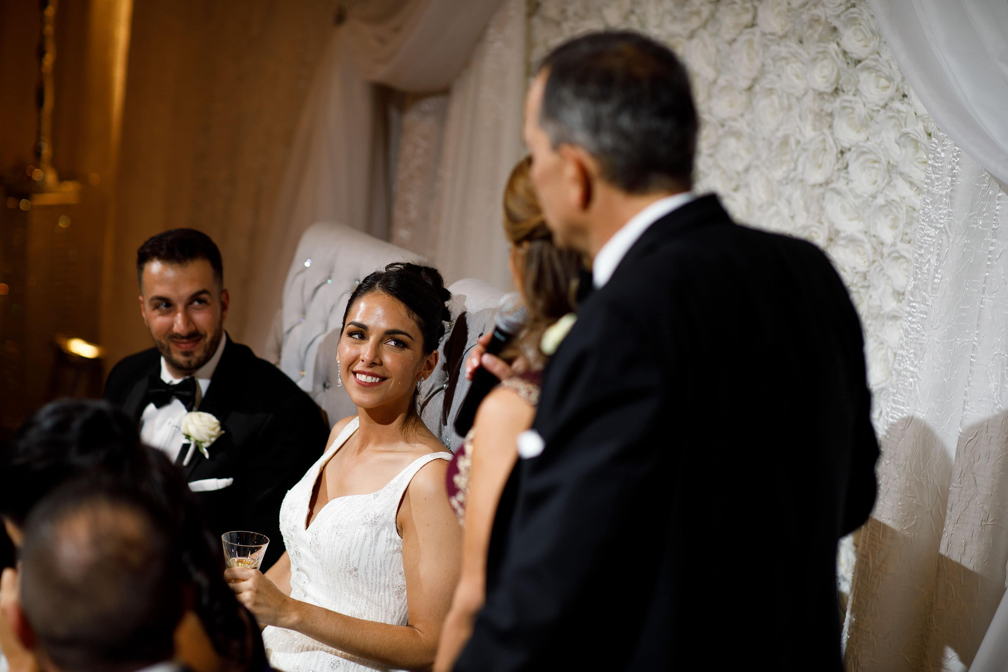 The bride smiles during a toast