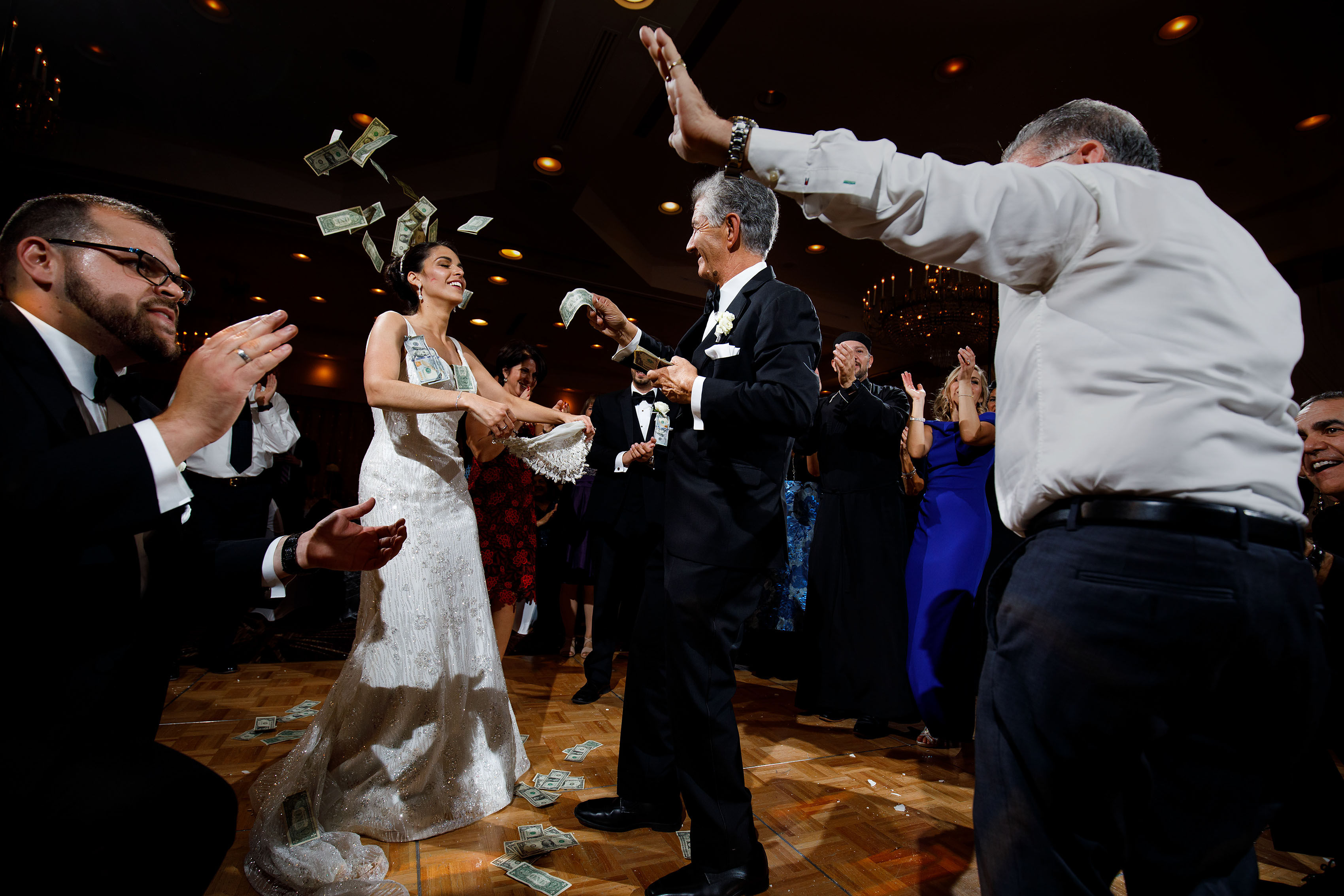 The father of the bride makes it rain dollar bills on the dance floor