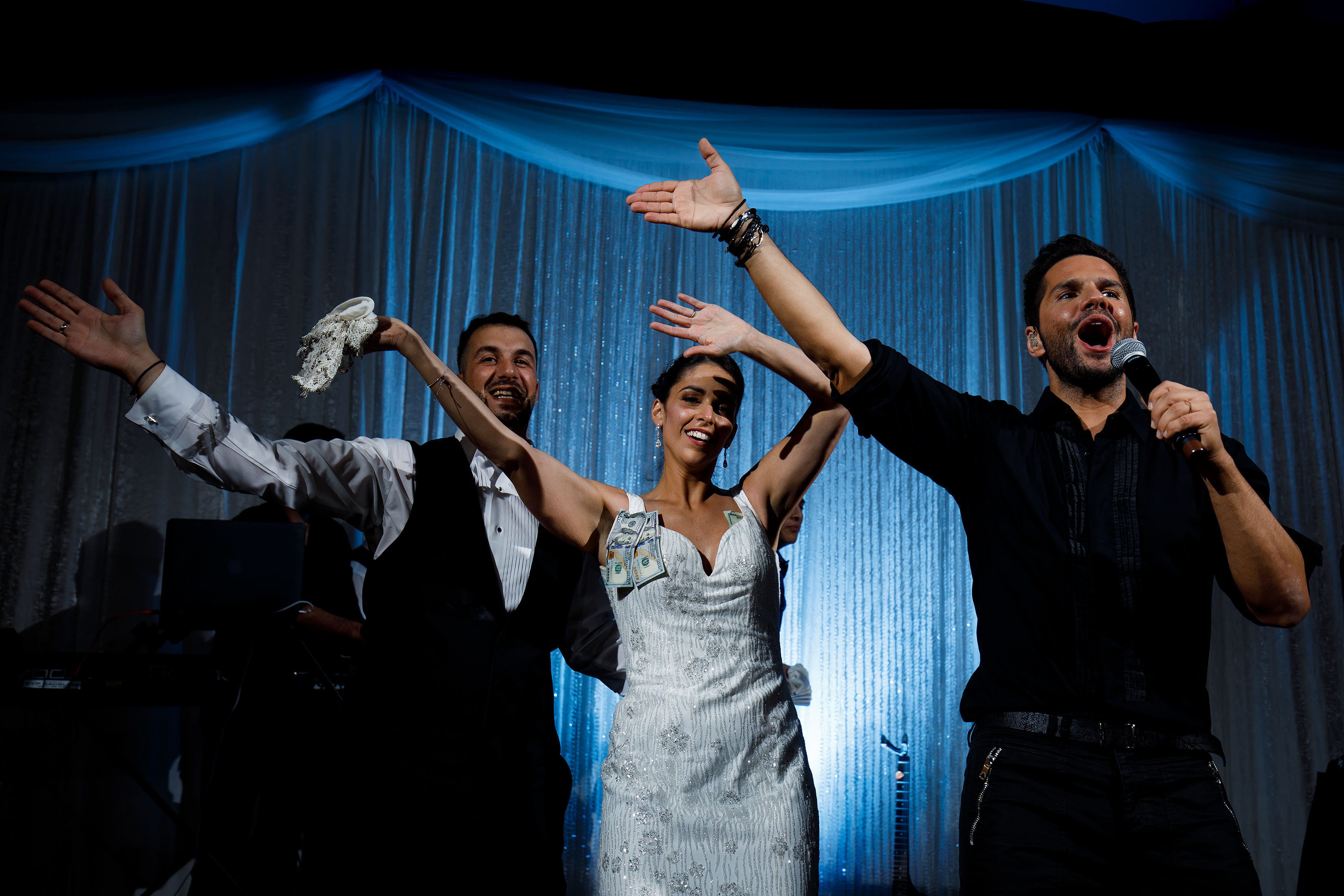The bride and groom dance on stage as Greek pop artist Giorgos Tsalikis performs during their Albuquerque Greek Orthodox wedding reception at the Sheraton uptown