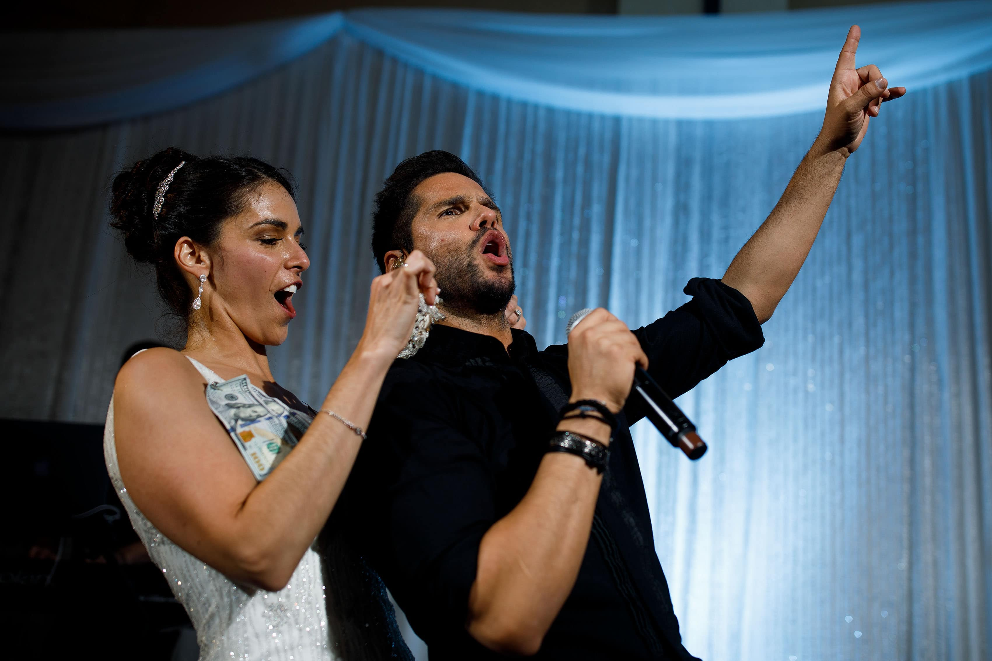 The bride dances on stage as Greek pop artist Giorgos Tsalikis sings during her wedding reception at the Sheraton Albuquerque uptown