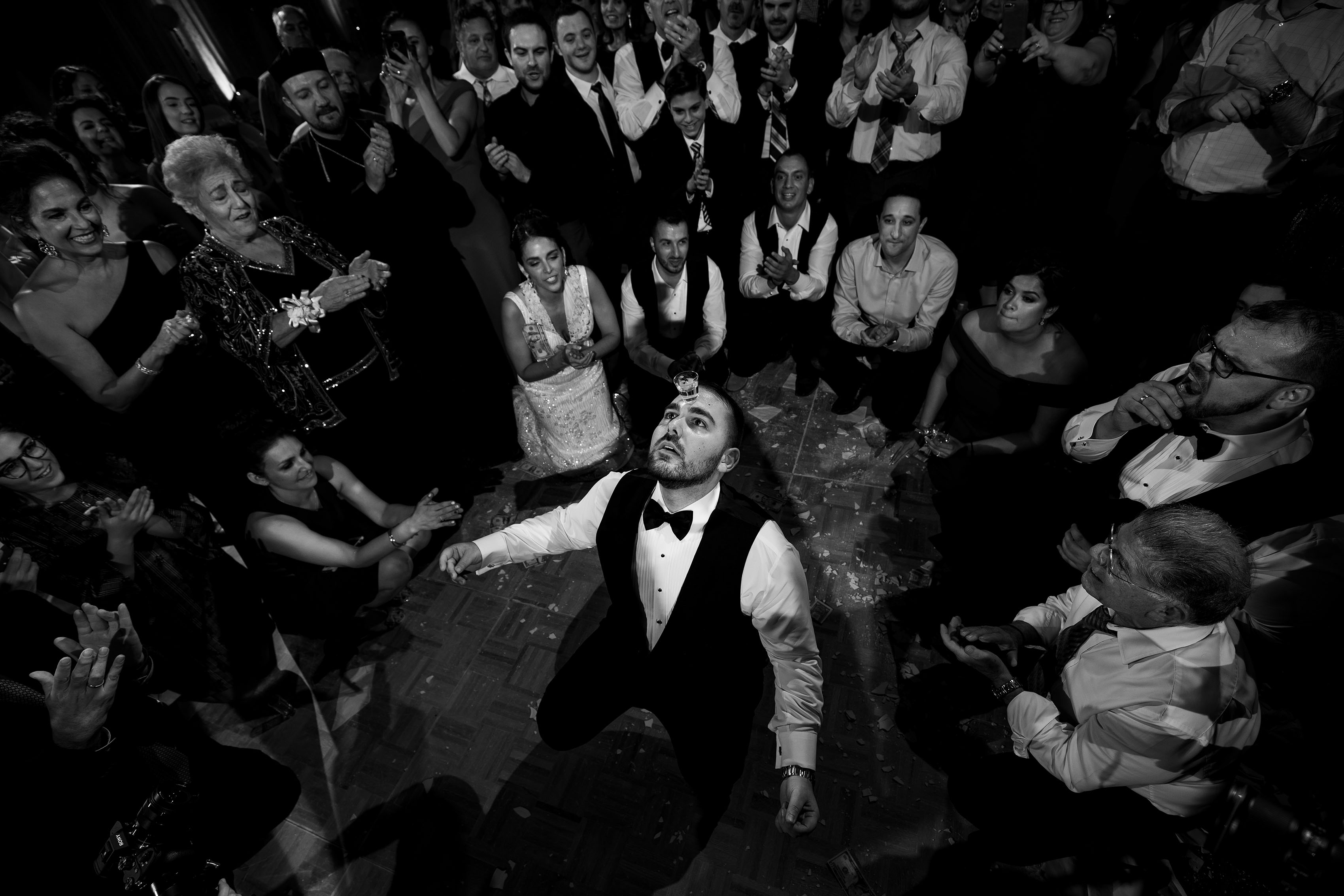 A guest dances with a shot of Ouzo on his forehead at a Greek wedding in Albuquerque at the Sheraton Uptown