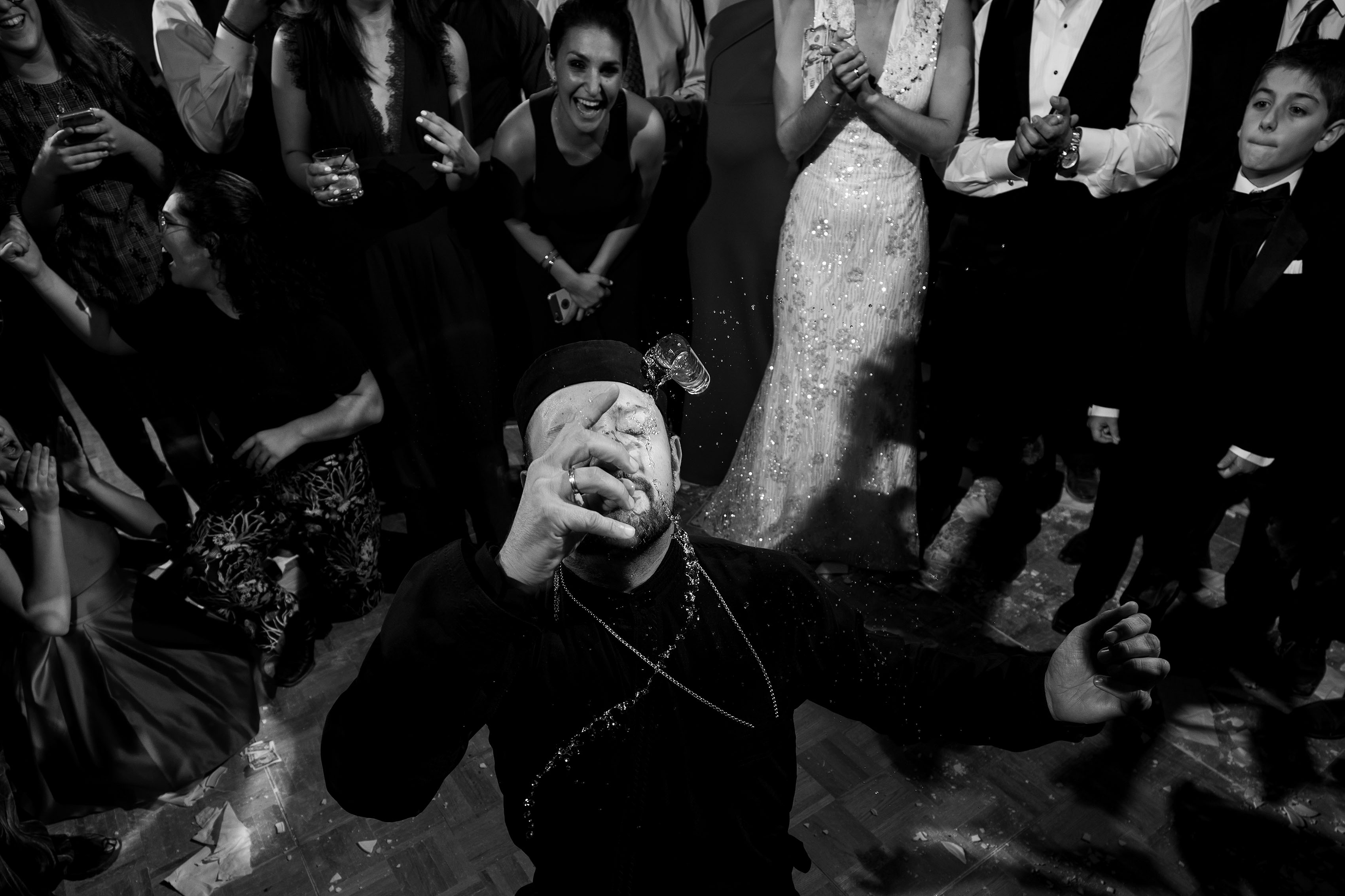The priest spills a shot of Ouzo on his face while dancing at a Greek wedding reception at the Sheraton Albuquerque uptown