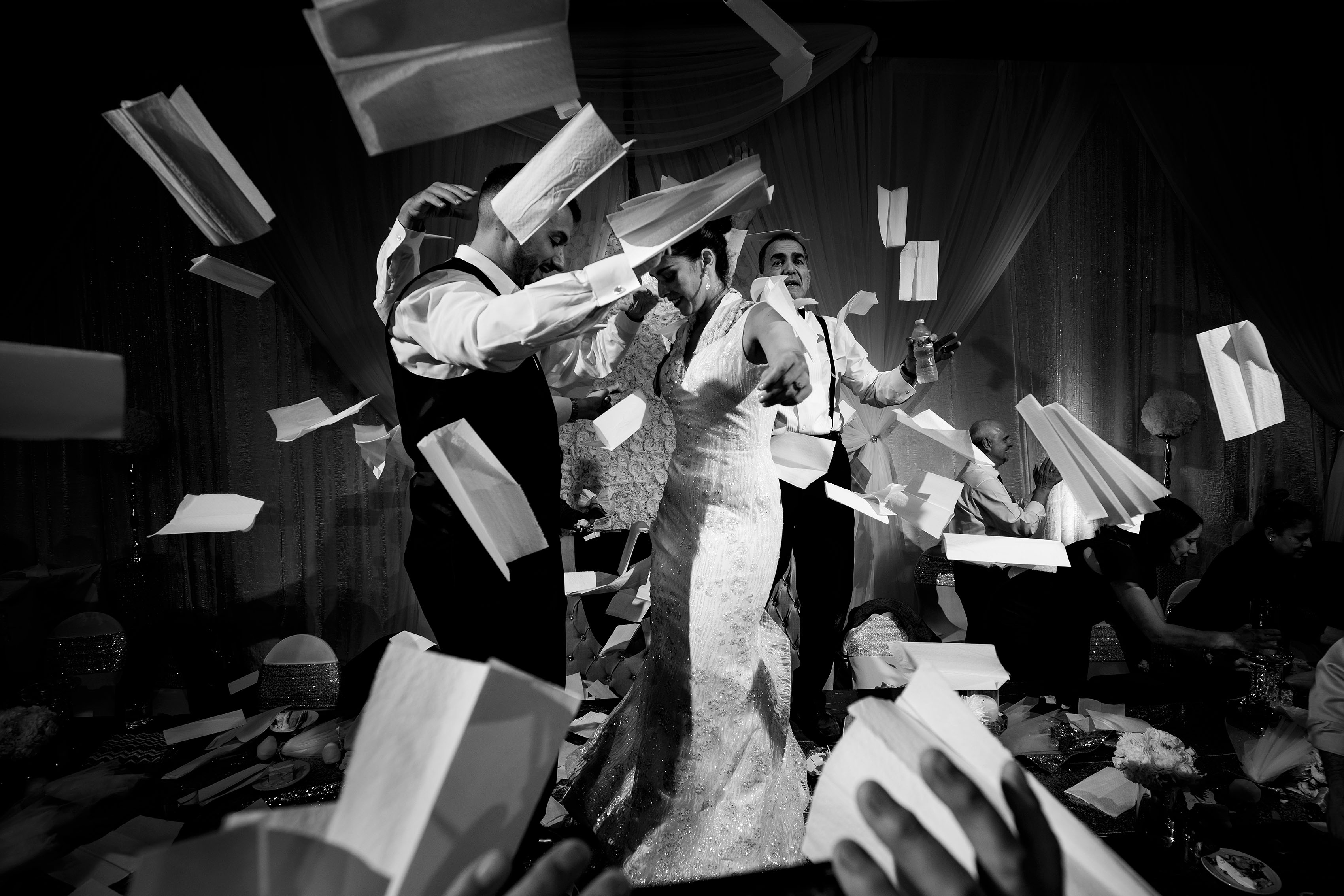 The bride and groom dance on a table as napkins fly around them during their traditional Greek wedding reception at the Sheraton Albuquerque uptown