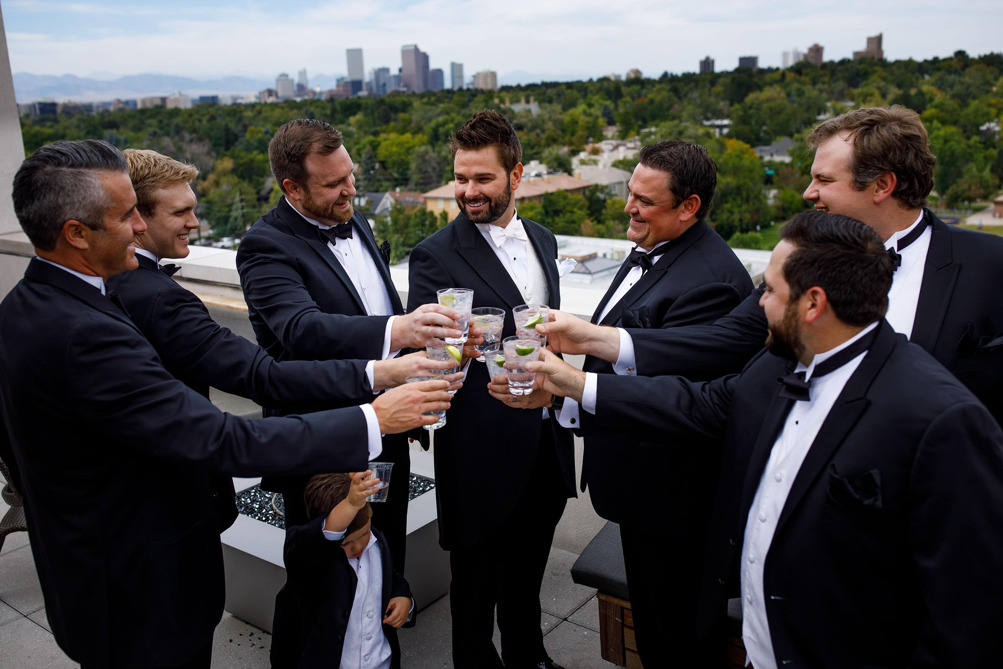 The groom and groomsmen toast from the rooftop at the Halcyon hotel in Denver before the wedding