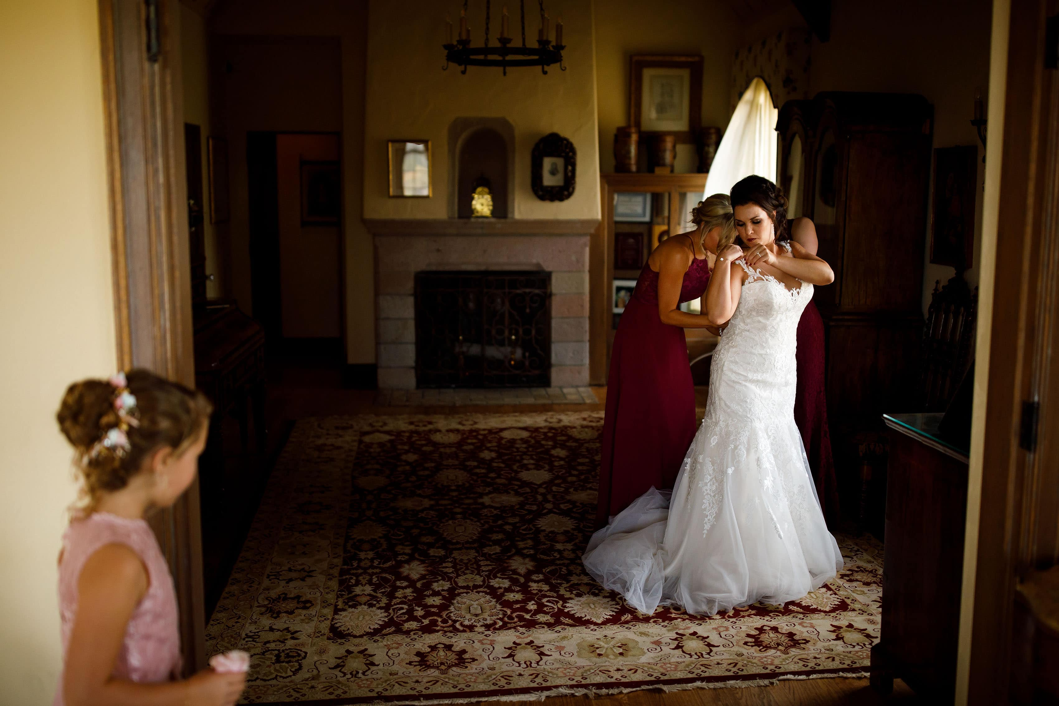 Melissa adjusts her wedding dress in the bridal suite as the flower girl looks on before her Cherokee Ranch & Castle wedding in Sedalia