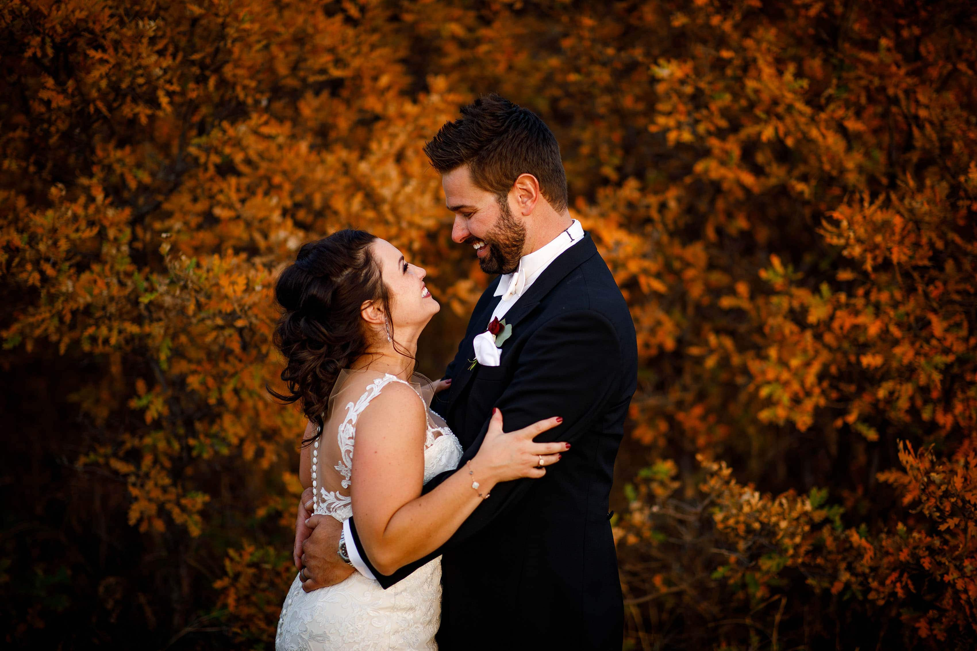 The couple embrace near a grove of fall color after their wedding in Sedalia
