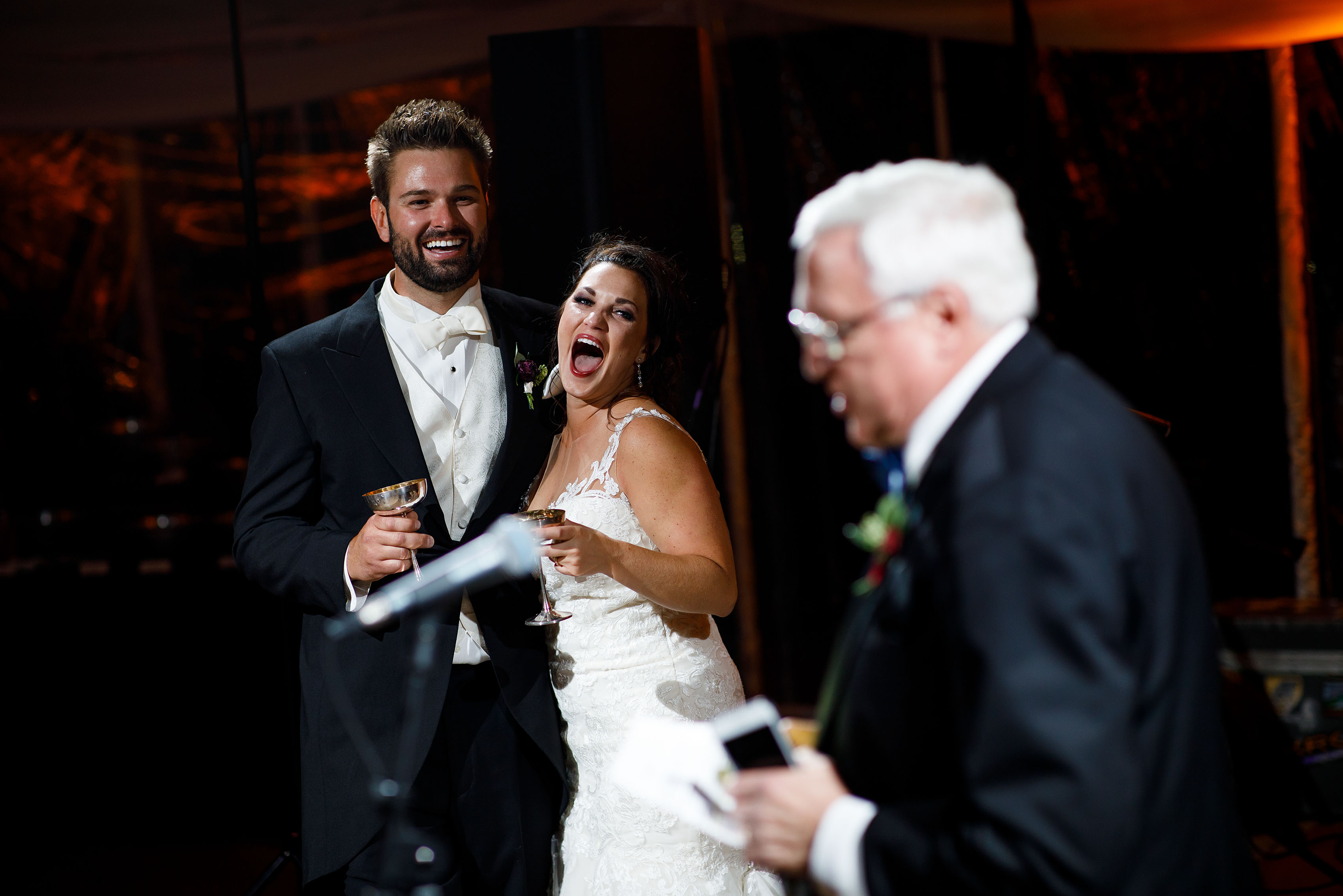 The couple react as the father of the bride gives a toast