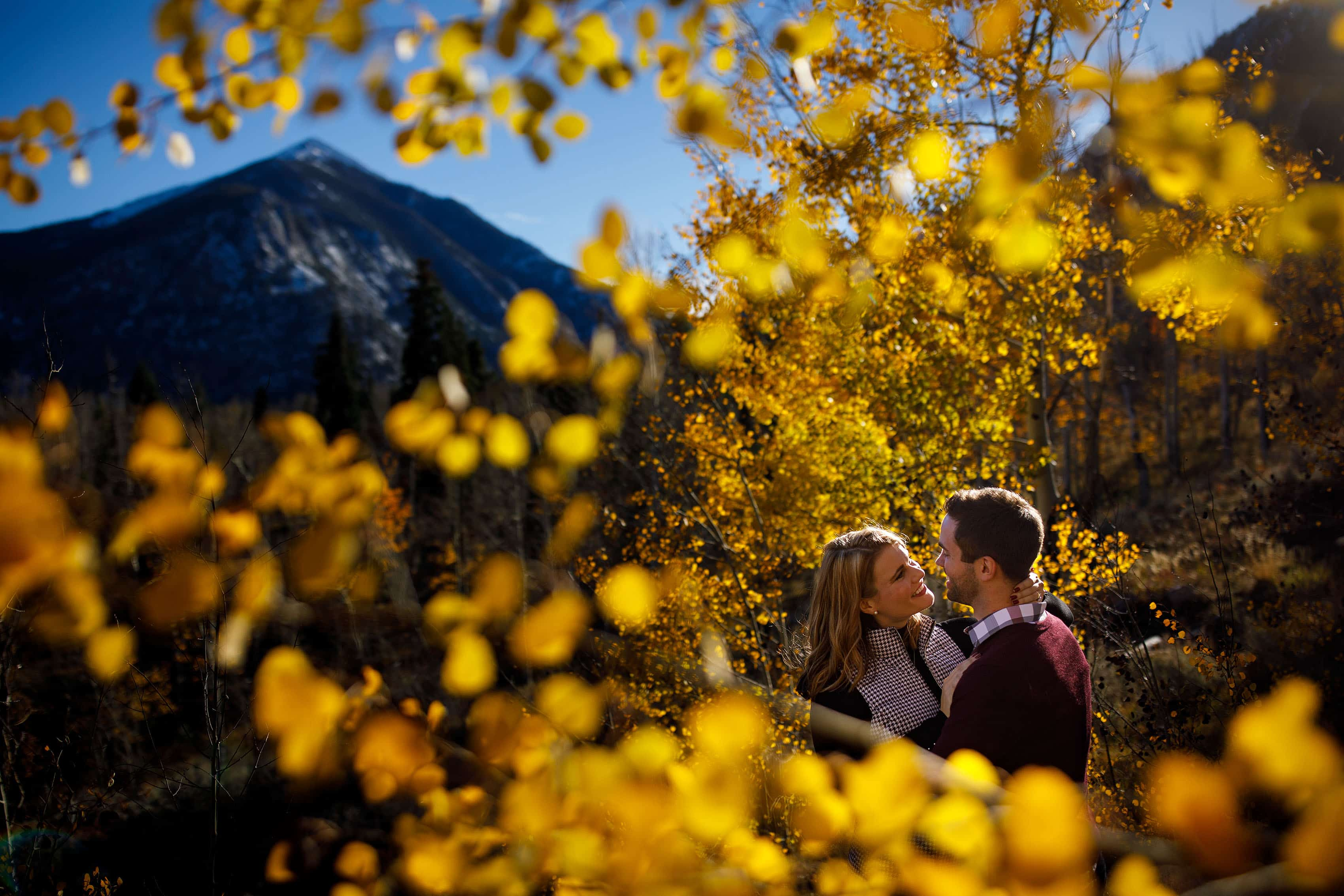 Julia and Micha embrace near golden aspen trees during their fall Frisco engagement photos in Colorado