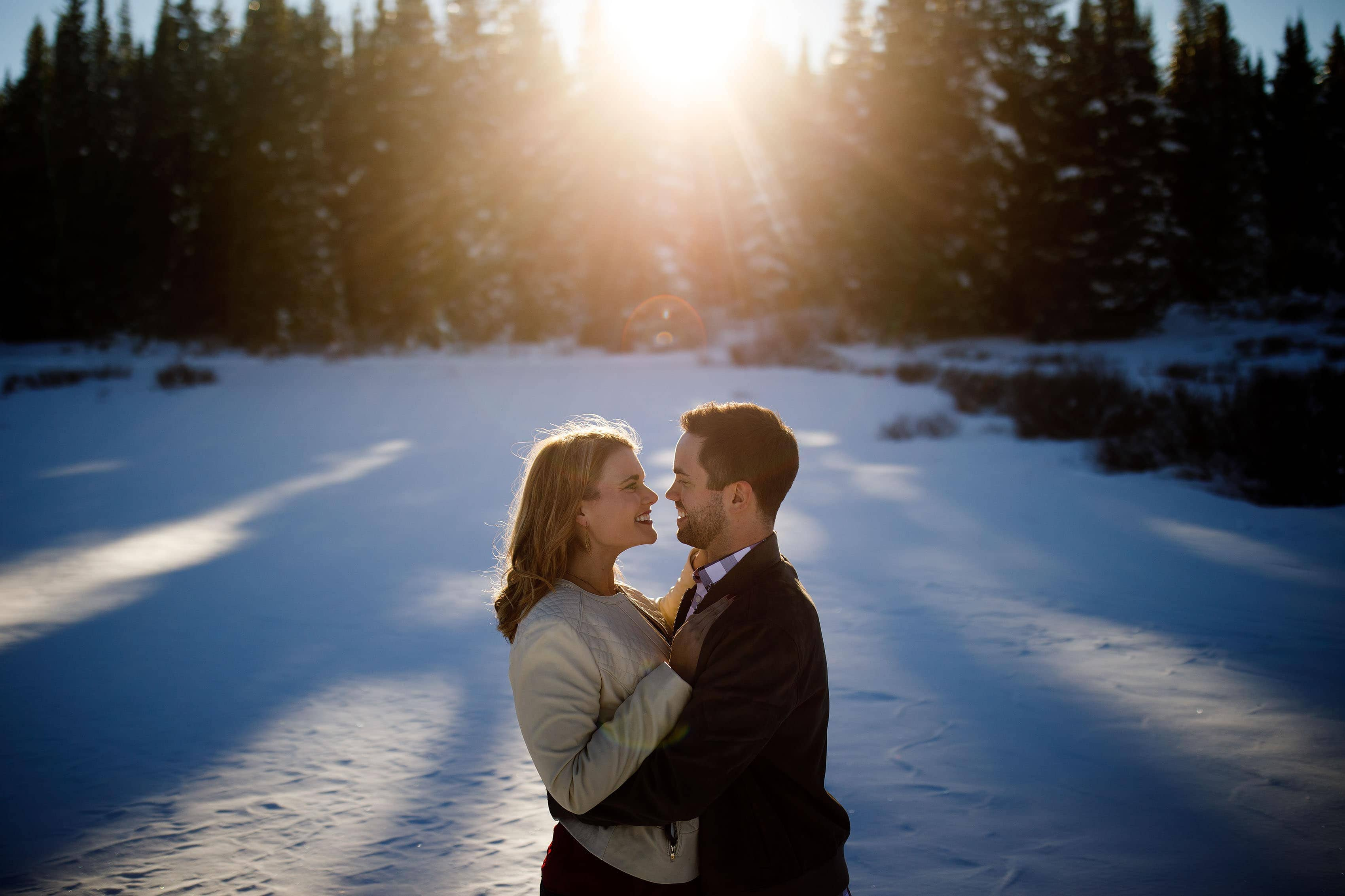 Micha and Julia pose together in the snow as the sun sets behind them on Shrine Pass near Vail