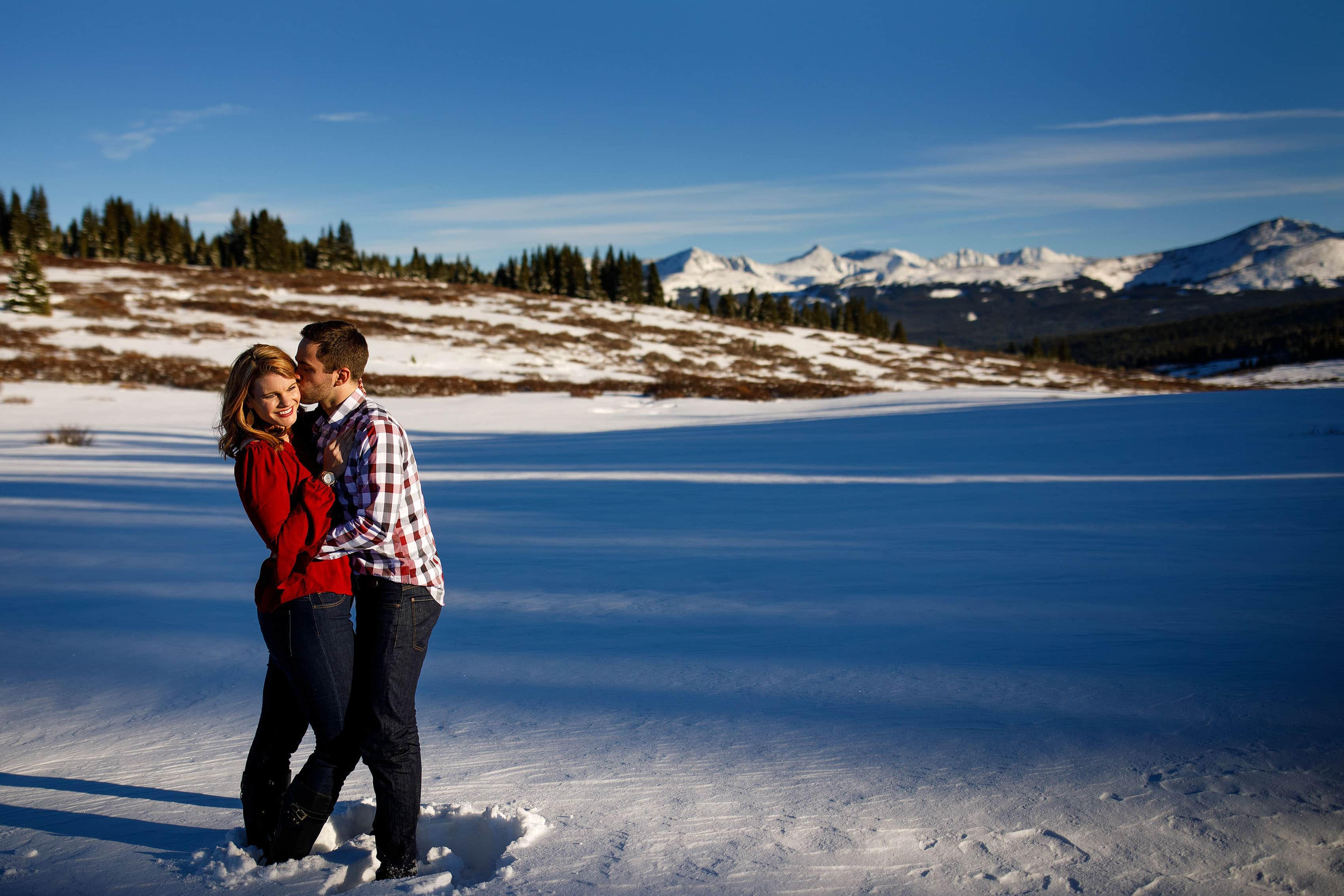 Micha kisses Julia during their fall engagement session atop Shrine Pass near Vail