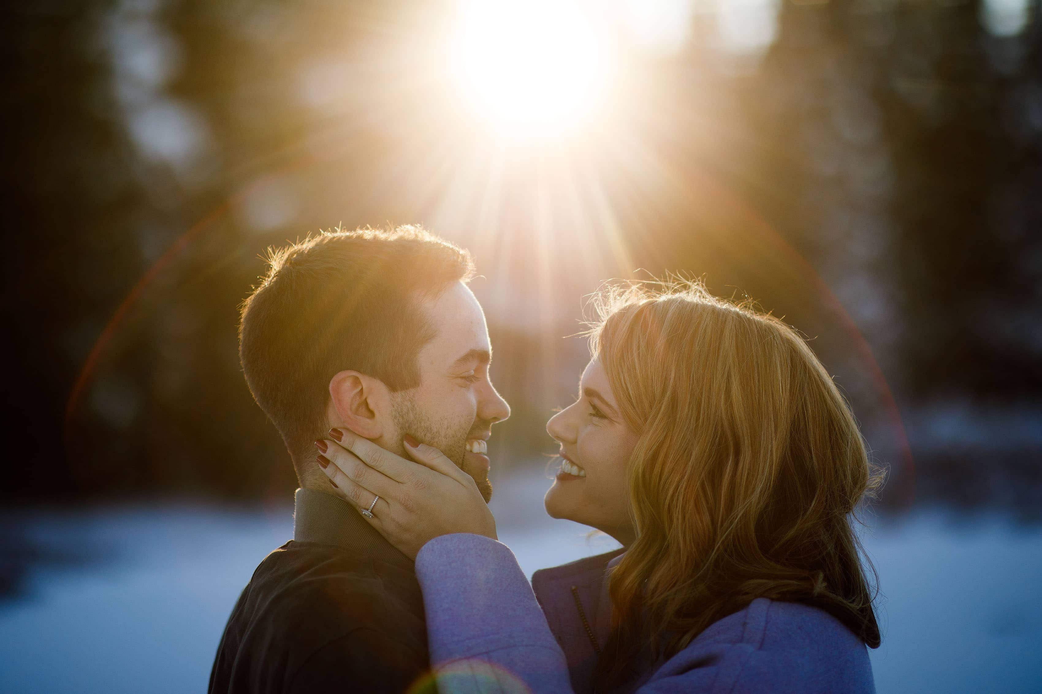 The future newlyweds embrace as the rays of sunlight disappear behind the trees during their fall engagement photos in Vail on Shrine Pass