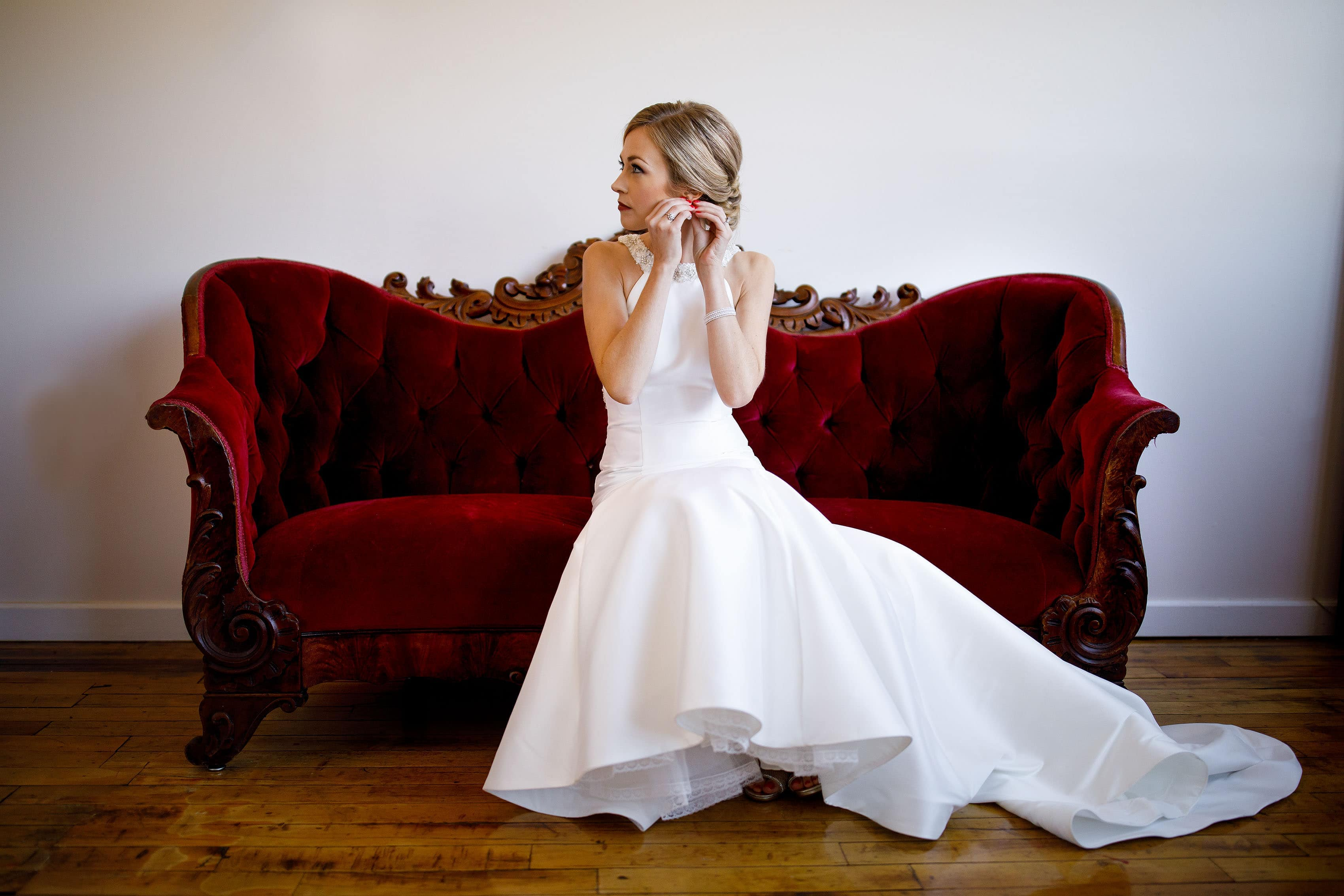 The bride puts on her earring on a red vintage couch before her Madison at the Mill wedding