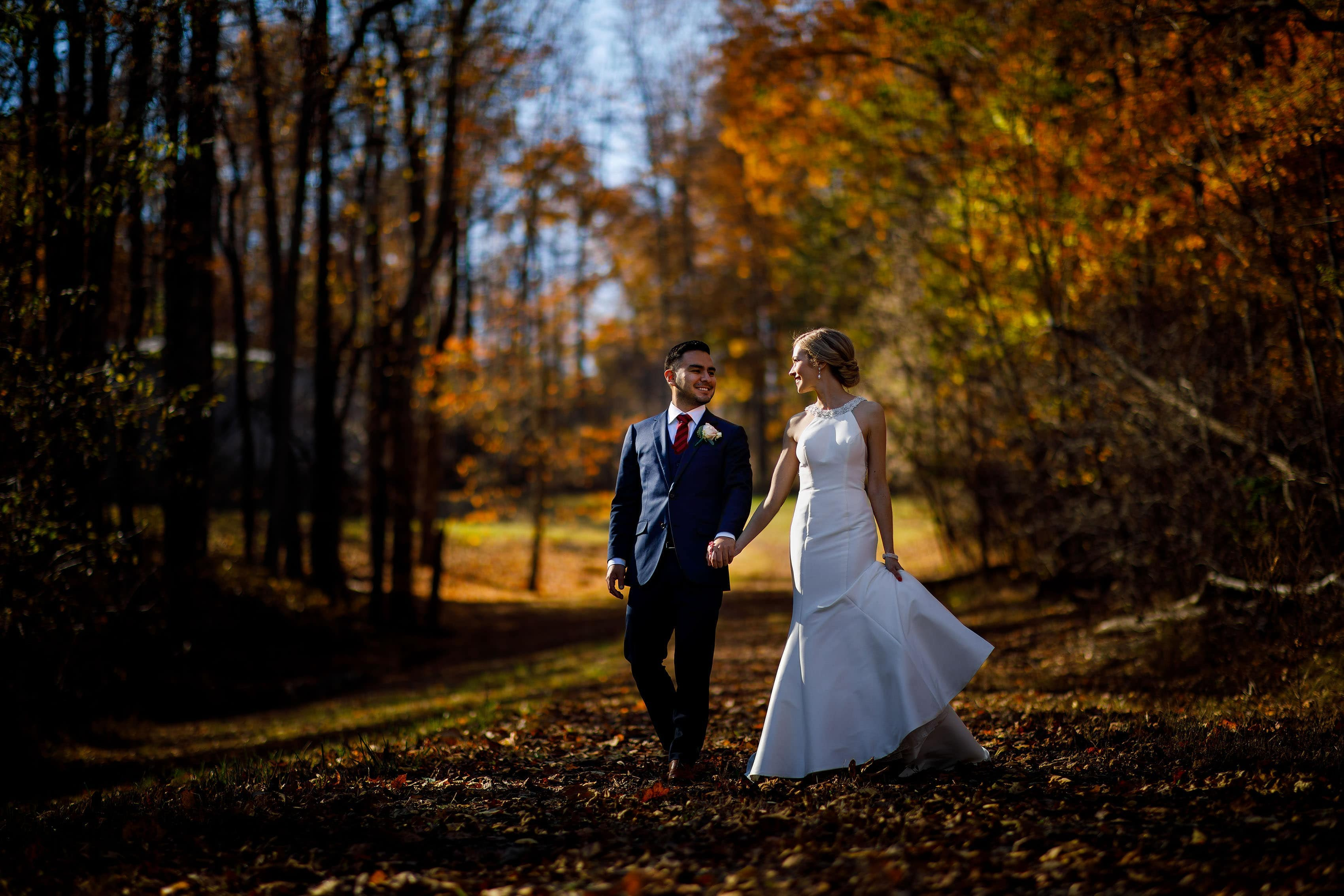 The newlyweds walk together surrounded by fall color before their Madison at the Mill wedding in Orange, Virginia
