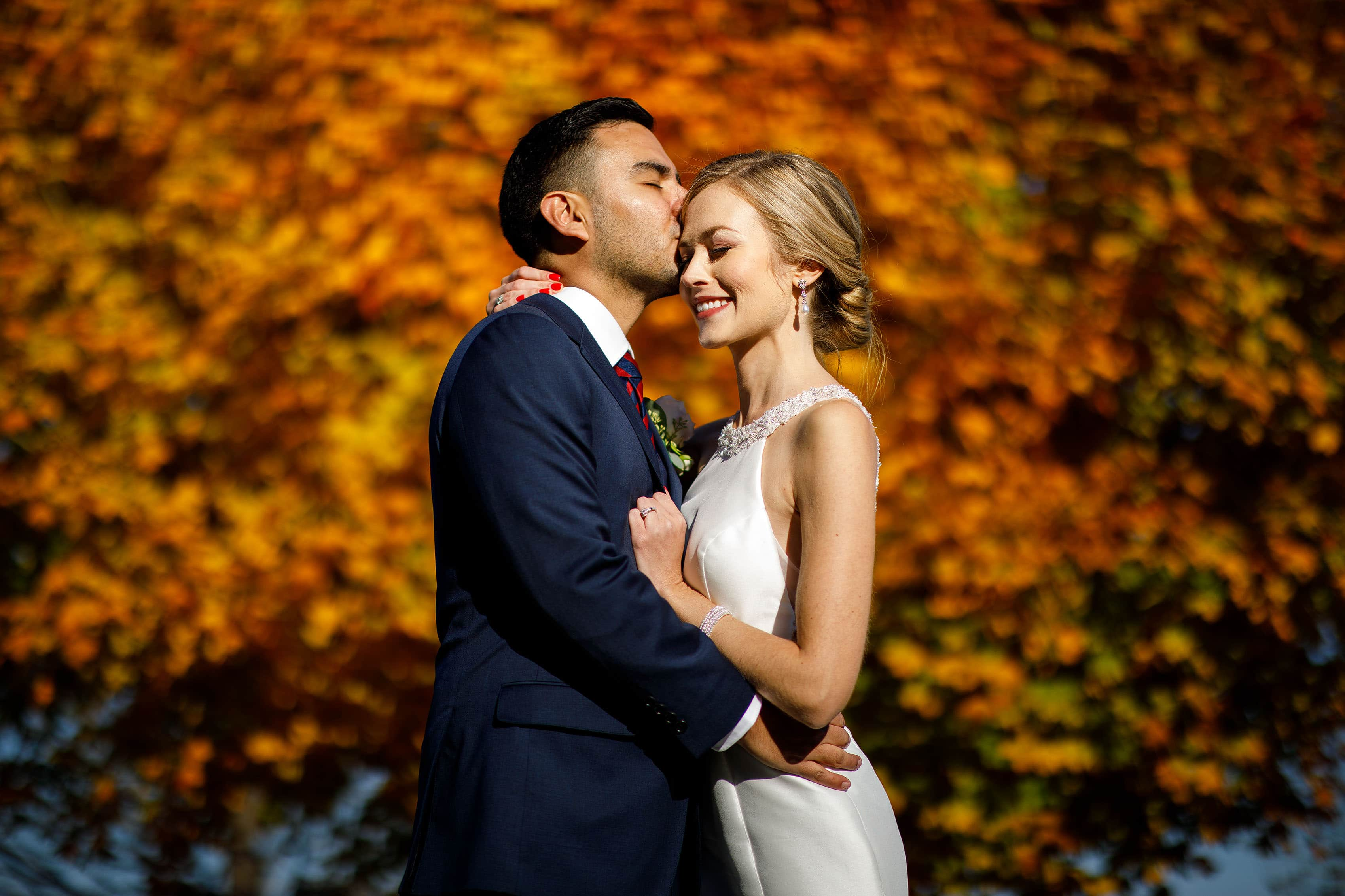 Richie kisses Ashley on their wedding day in Orange, Virginia near a colorful tree on a fall day