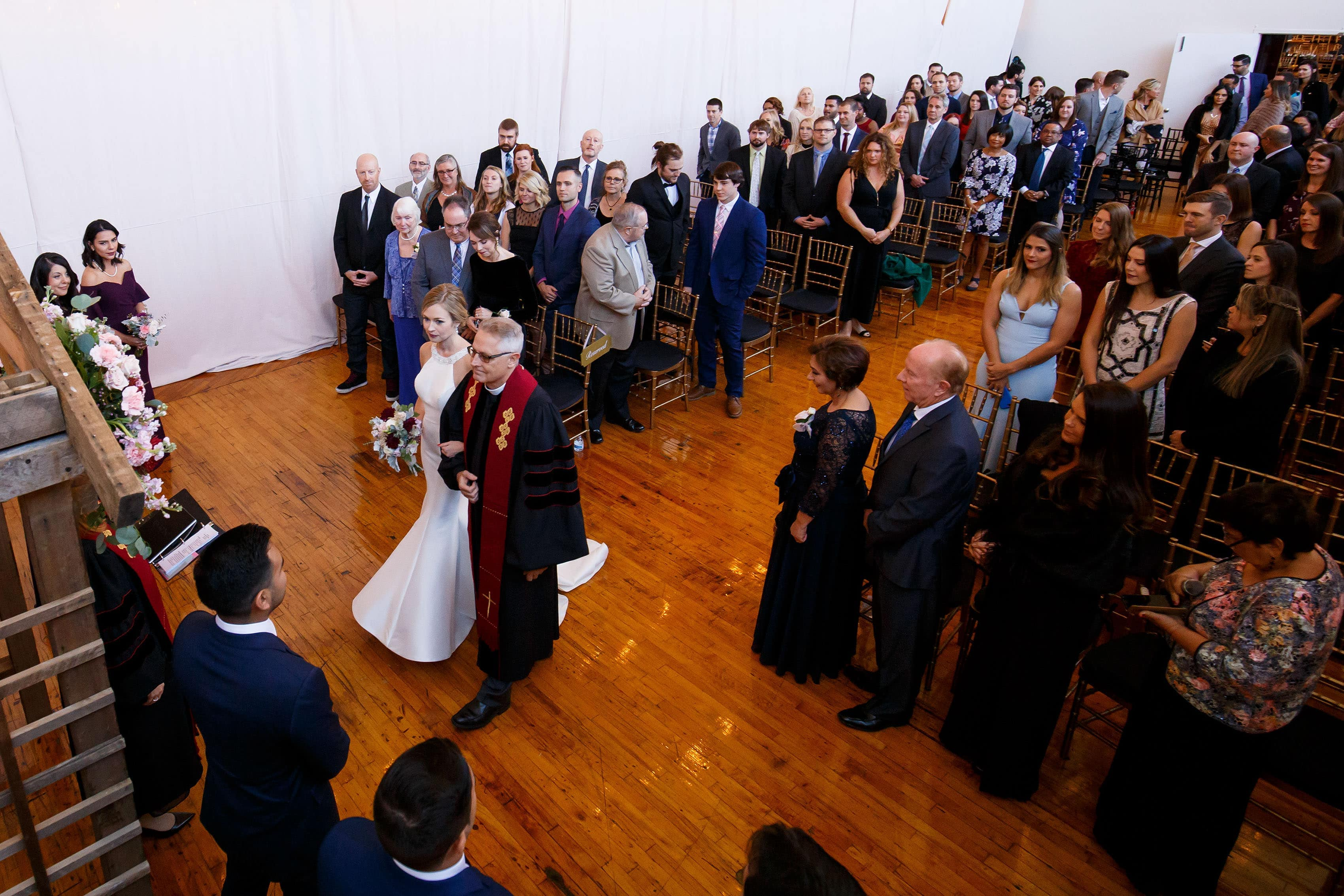 Ashley walks down the aisle with her father during her Madison at the Mill wedding ceremony indoors in Orange, Virginia