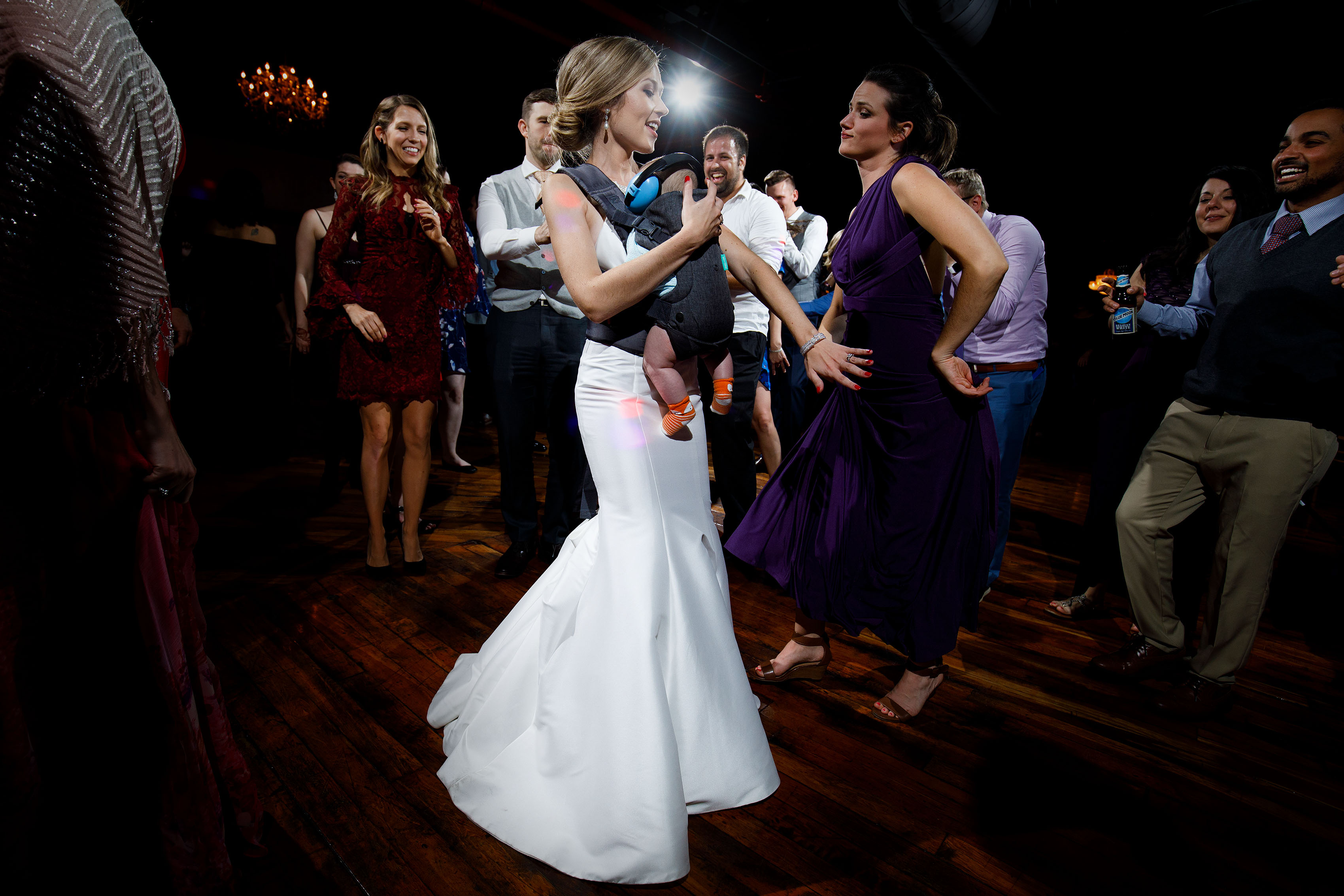 The bride dances with a newborn during her Madison at the Mill wedding
